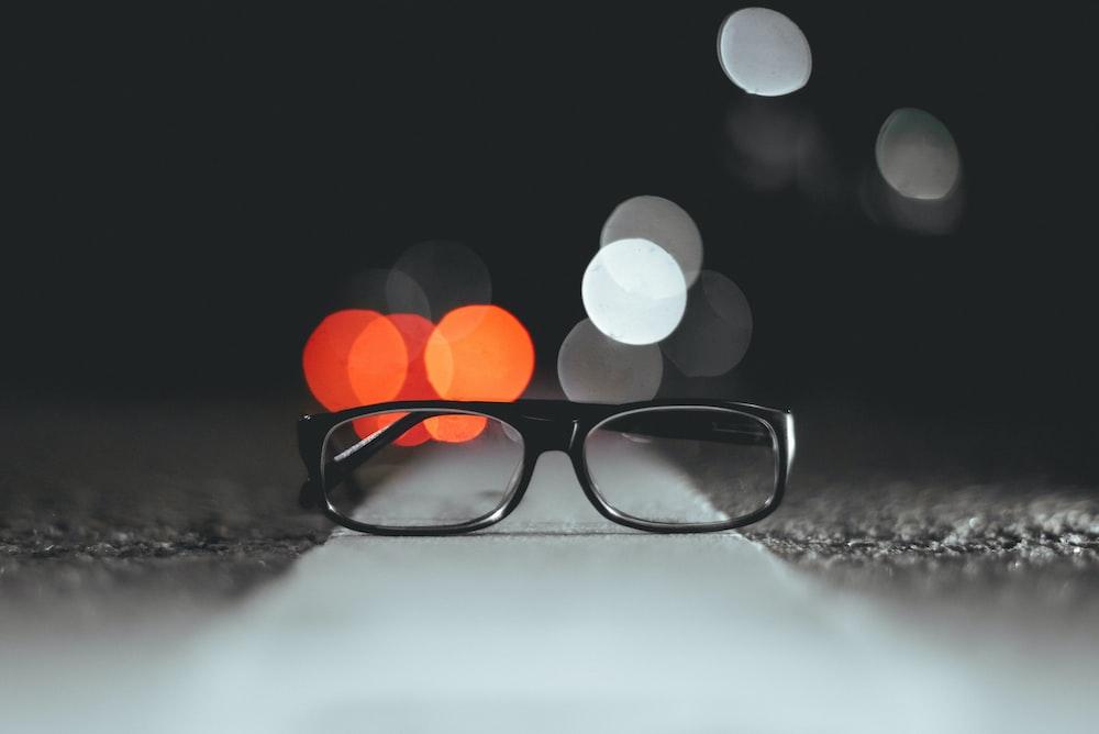 bokeh light photography of eyeglasses on pavement