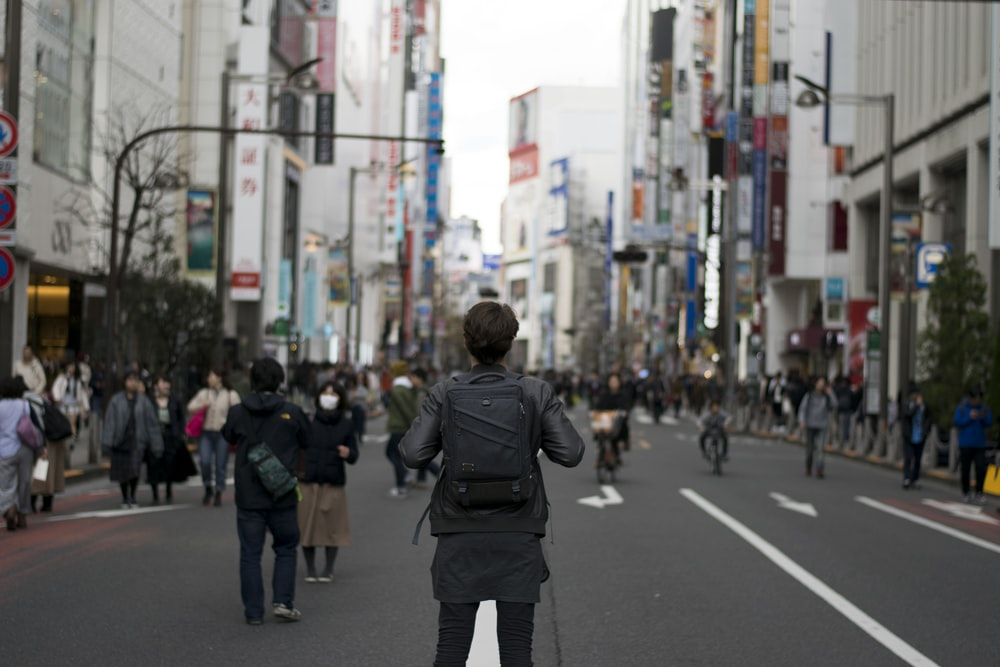shallow focus photography of person carrying backpack