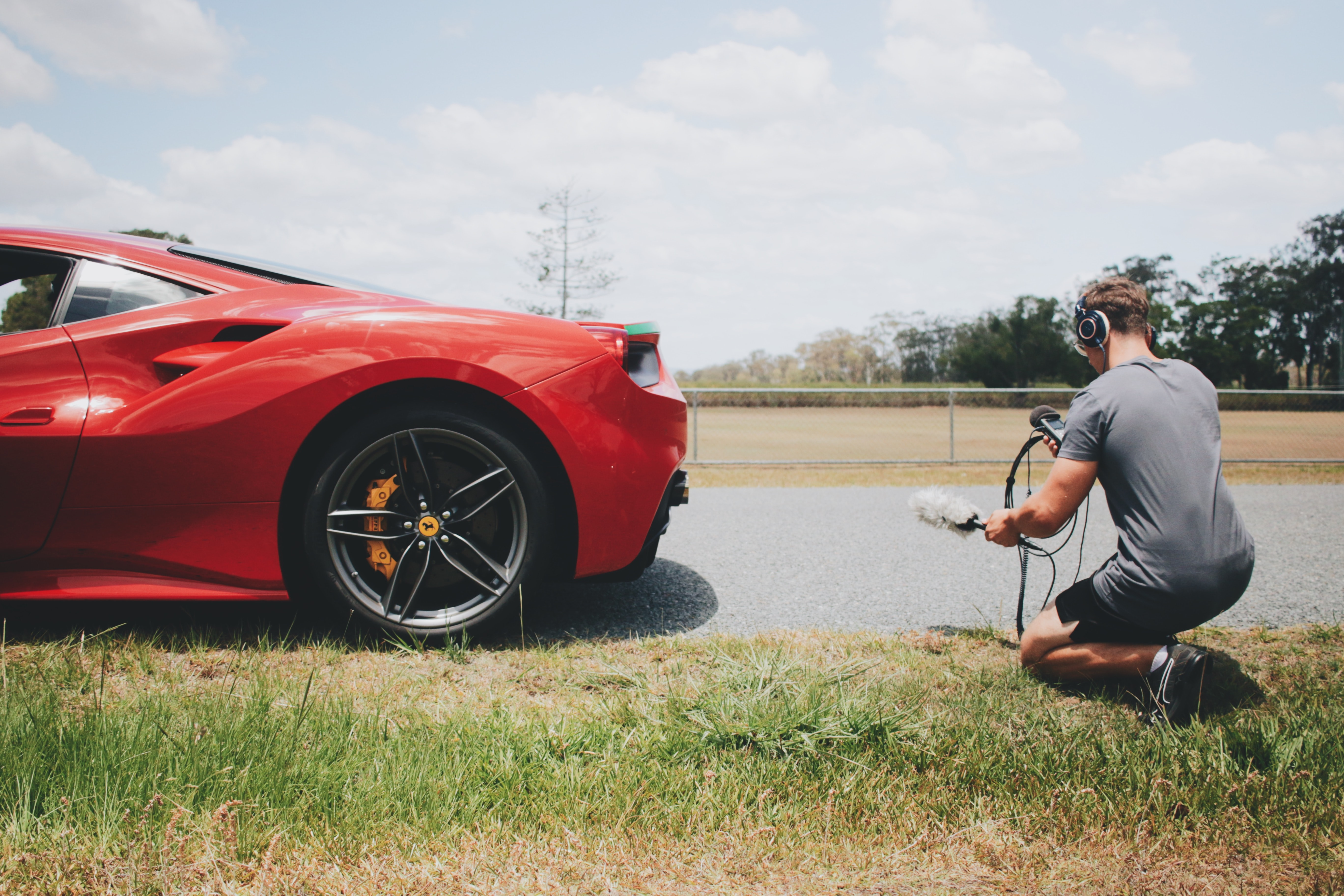 A videographer filming something about a car on the side of the road on the Gold Coast