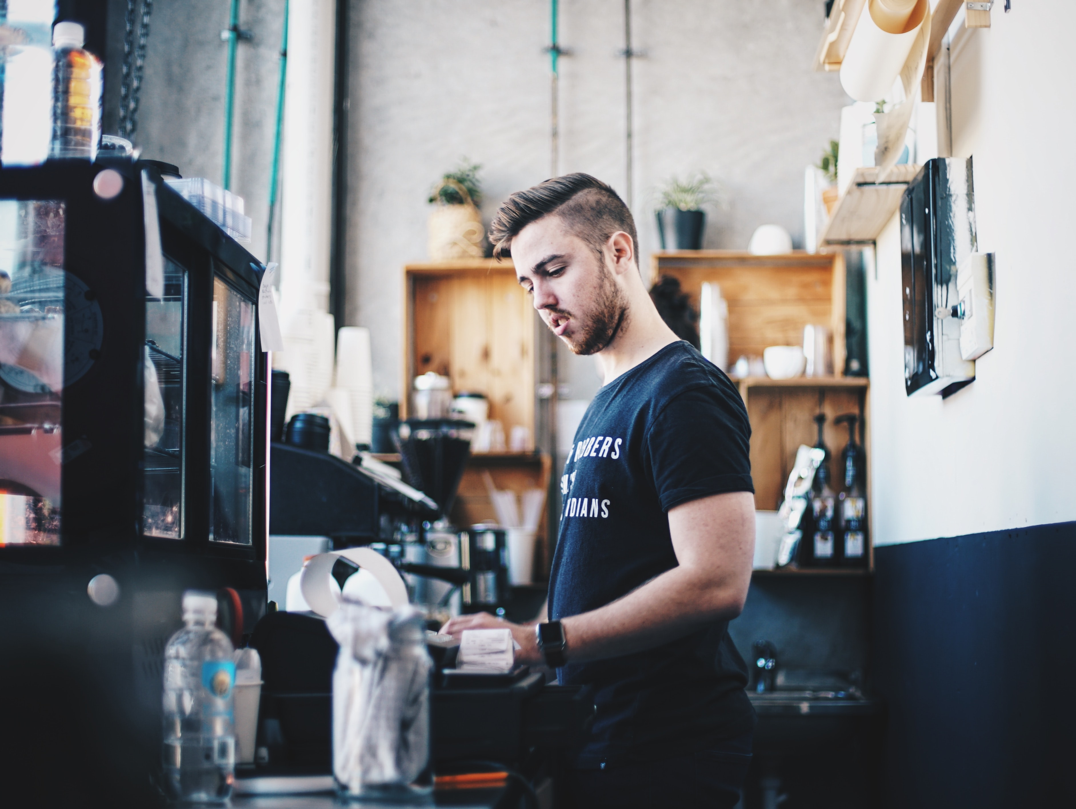 A barista working behind a cafe counter at a hipster coffee shop
