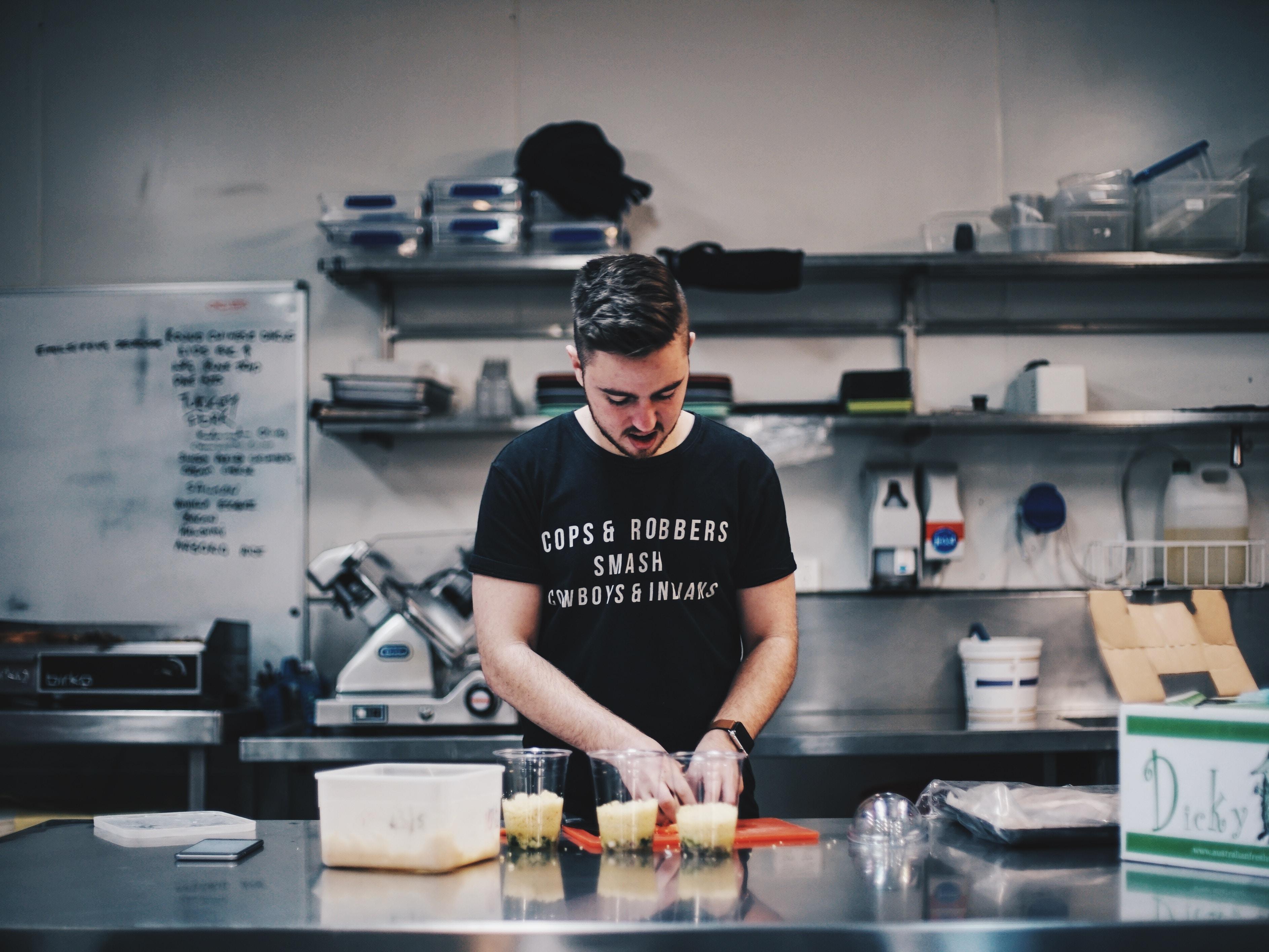 A man in a black t-shirt preparing food in a restaurant