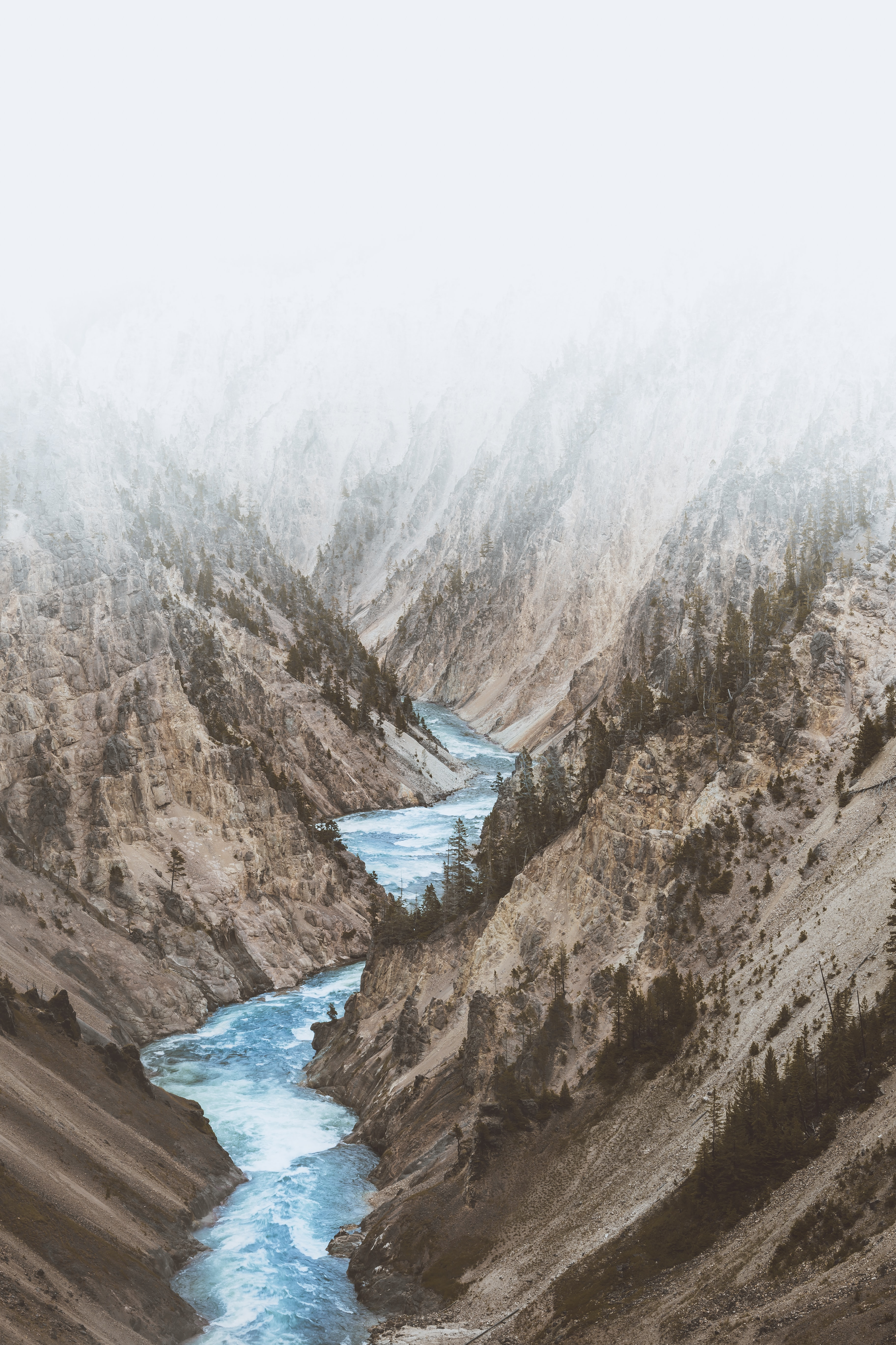 A river rushes through the valley of deserted mountain sides in Yellowstone