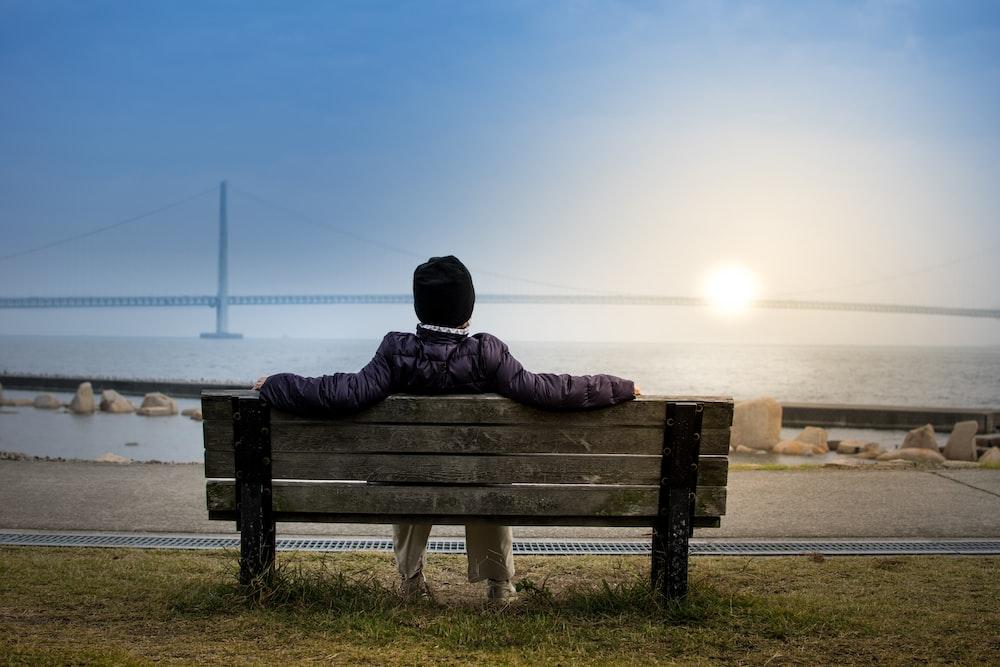 person sitting on bench facing suspension bridge