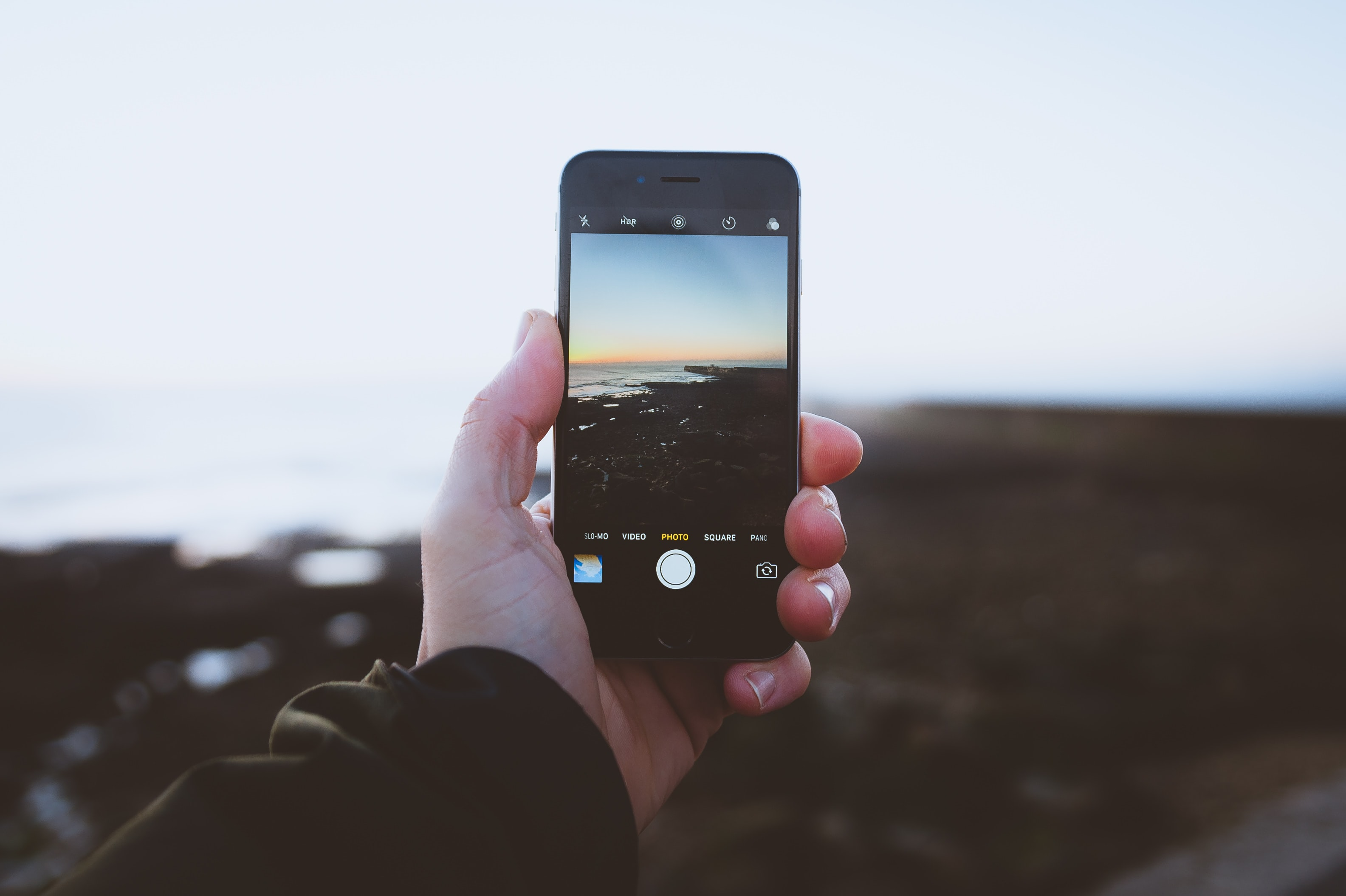 A man is taking a photograph of the sea with his iPhone.