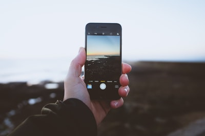person taking photo of landscapes using iphone during daytime device zoom background
