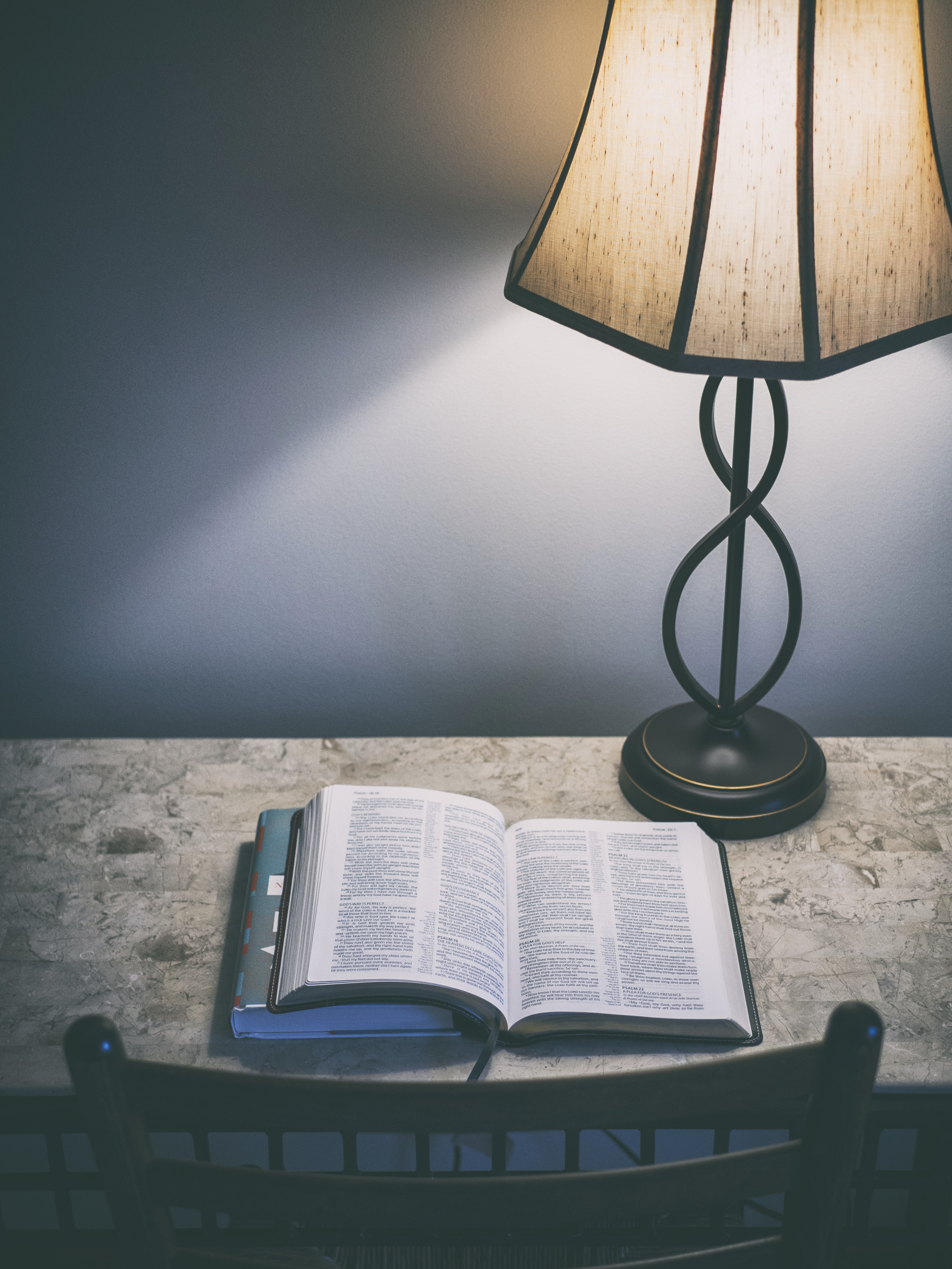 A book open on a table next to a lamp.