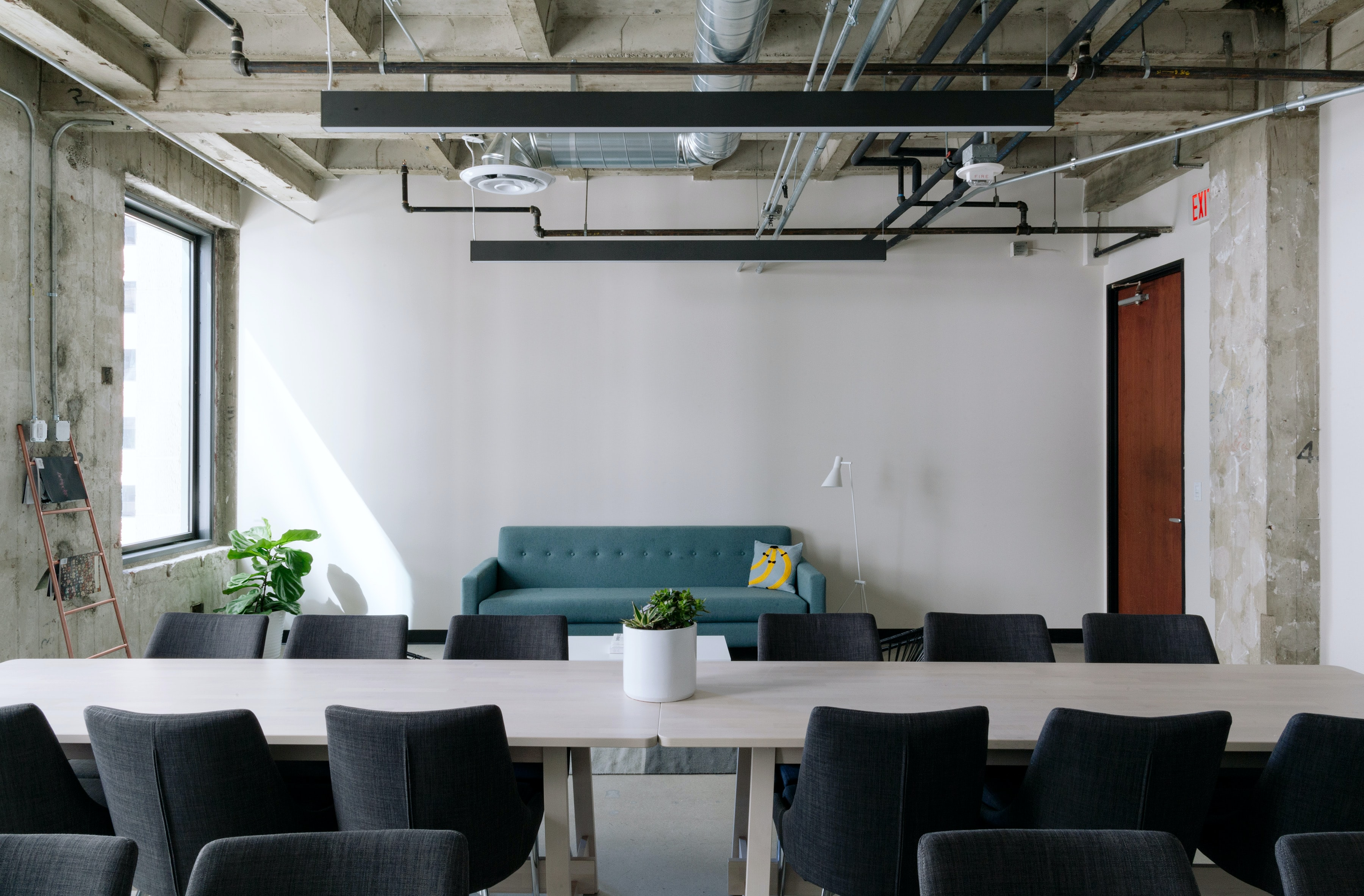 A meeting space in an office with two long tables and a sofa