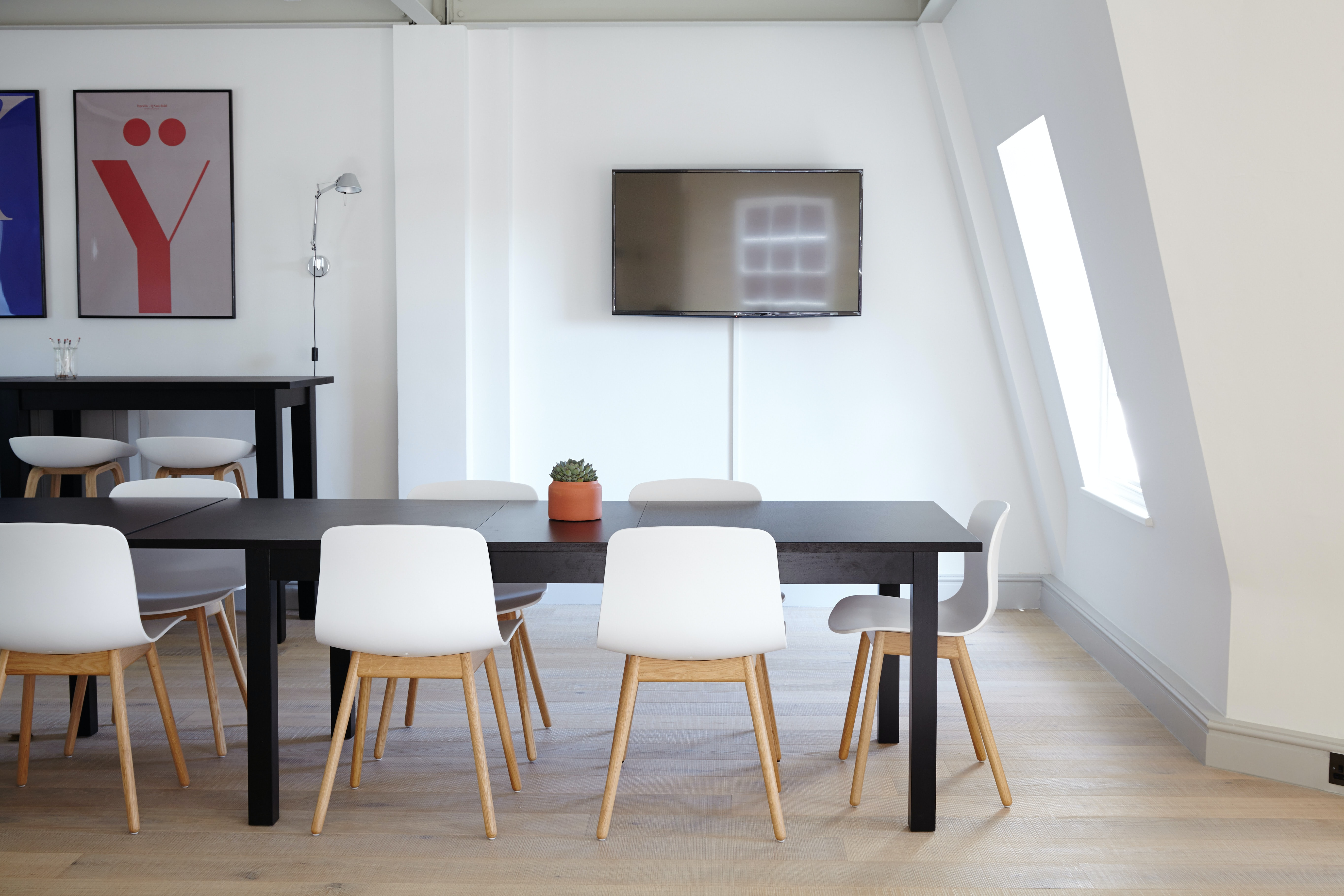 An Elegant Meeting Room With A Television On The Wall