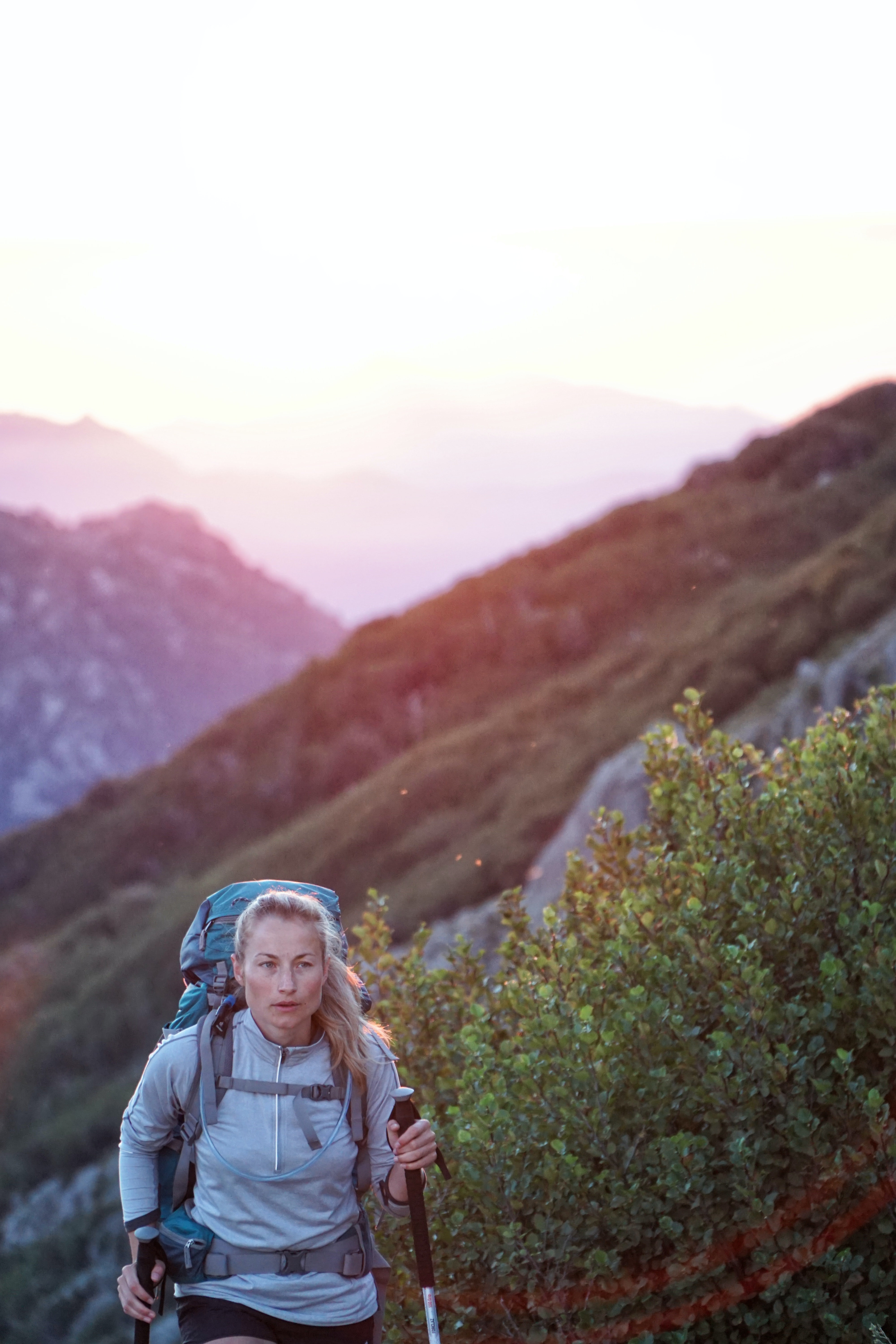 A blonde woman wears a backpack and uses walking poles while hiking near bushes, a sunset over mountains behind her