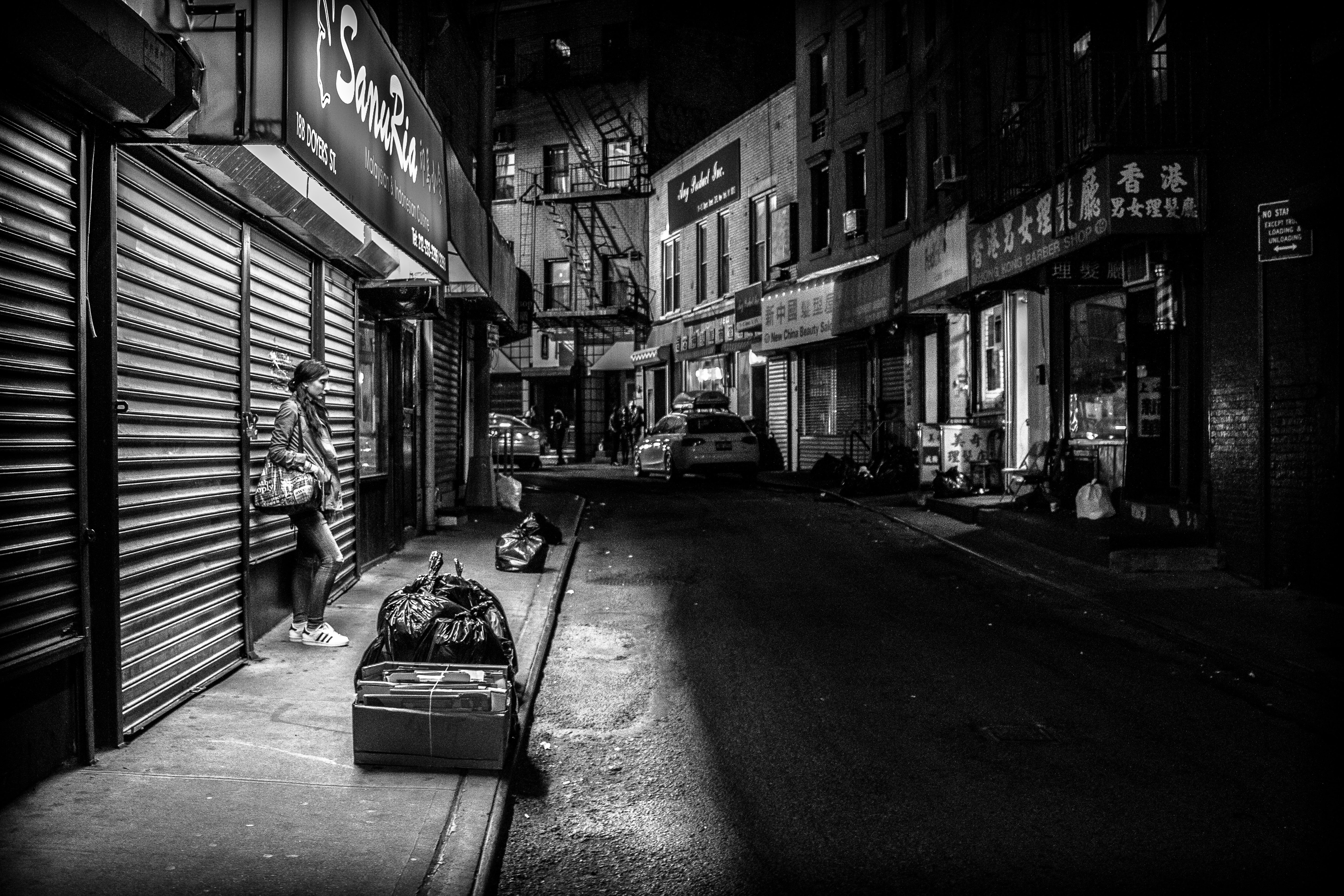 Black and white lone woman standing on sidewalk near closed storefront near garbage bags in Chinatown