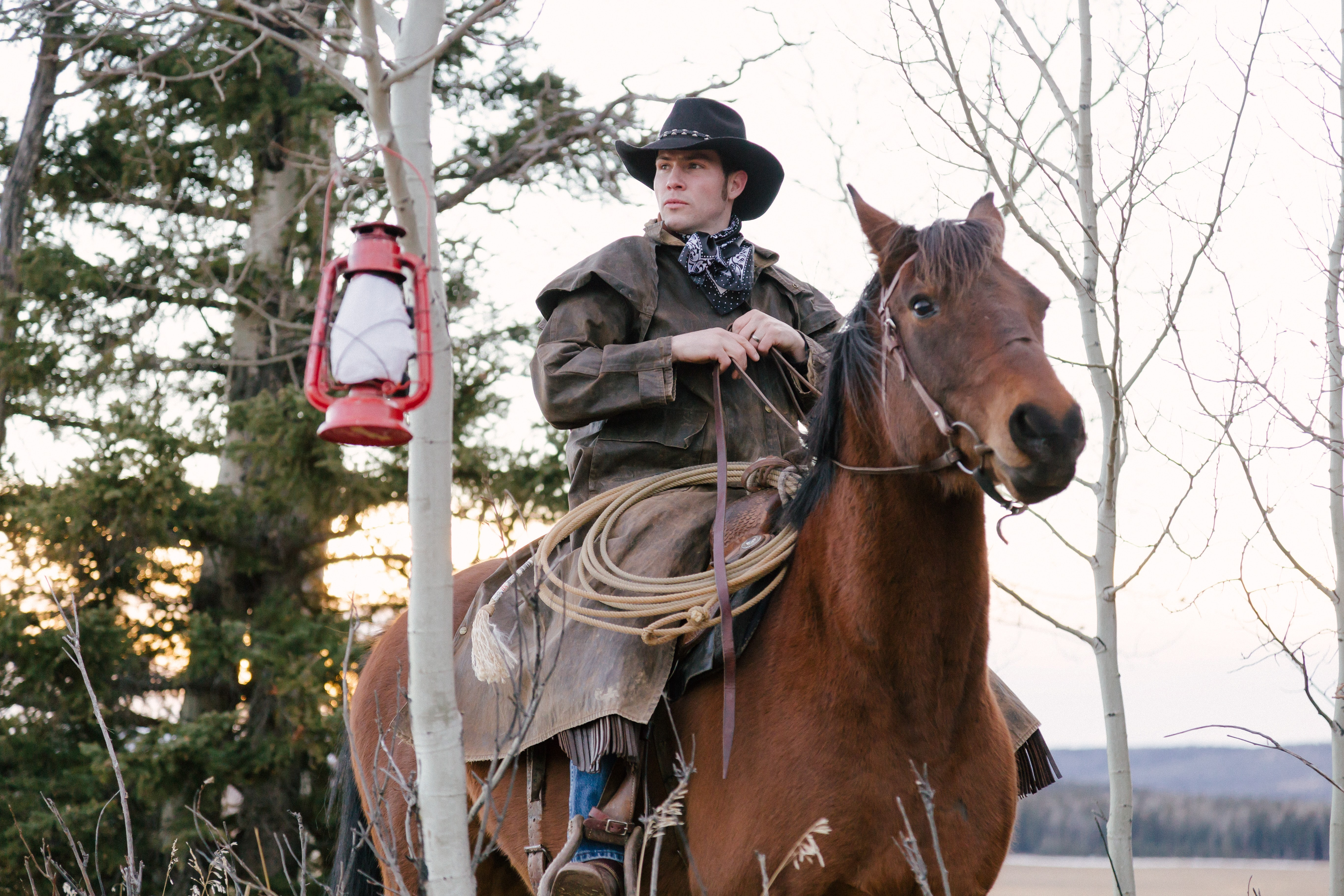 A man in a cowboy hat and a leather coat riding between trees on a chestnut horse