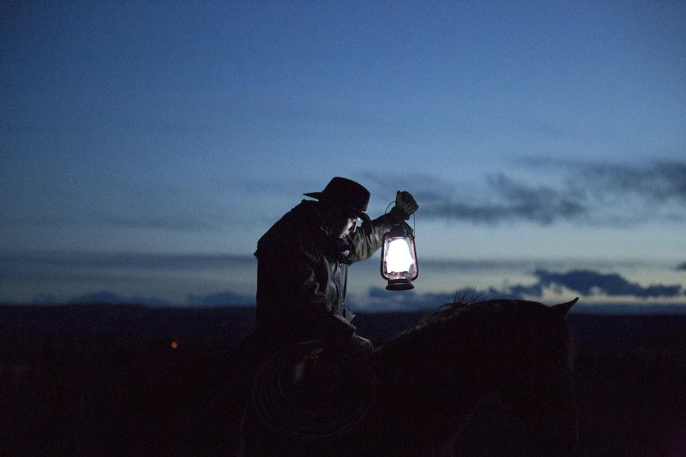 horseback riding cowboy holding a lamp