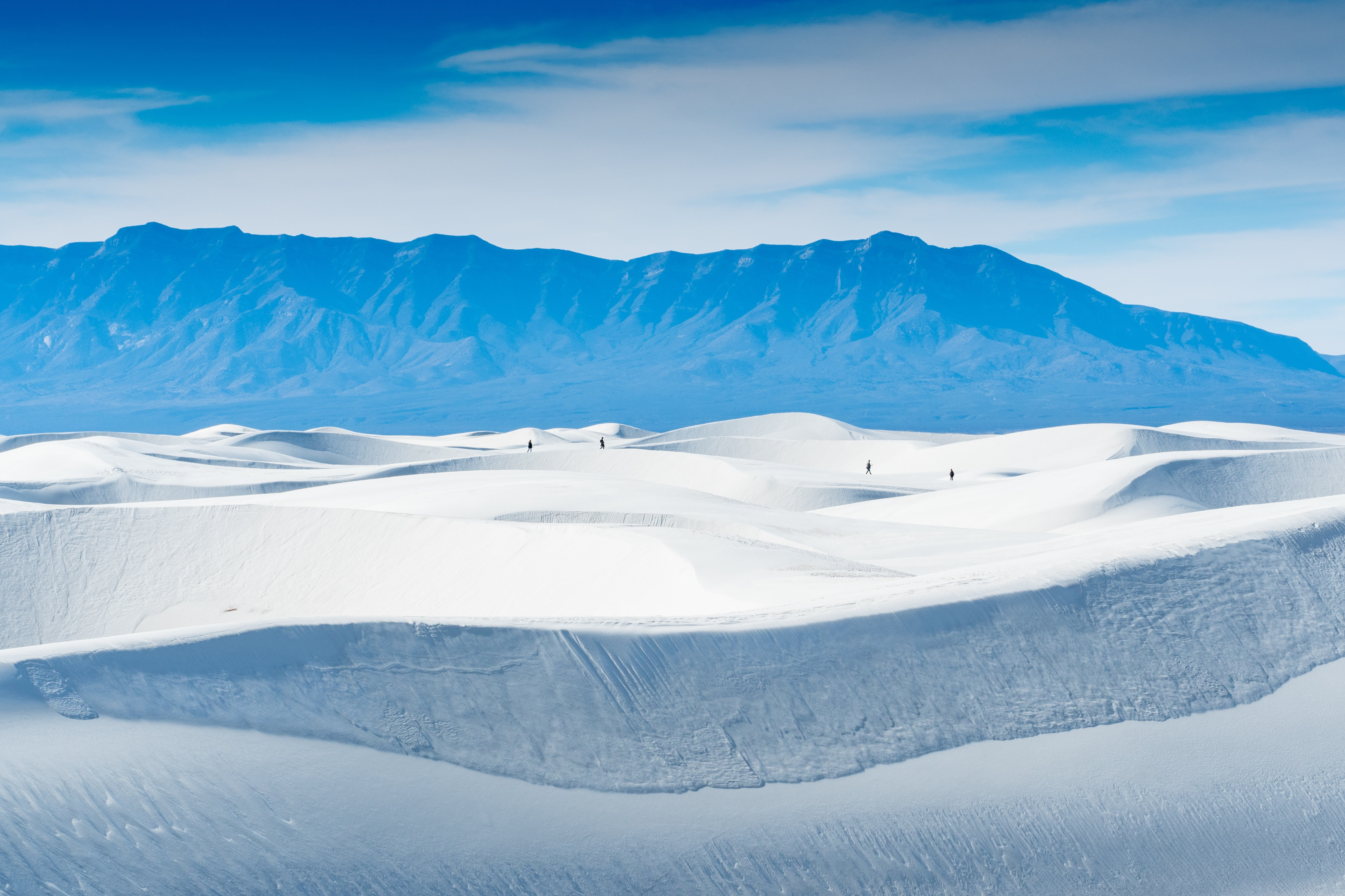 Hikers walk through the desert of White Sands National Monument