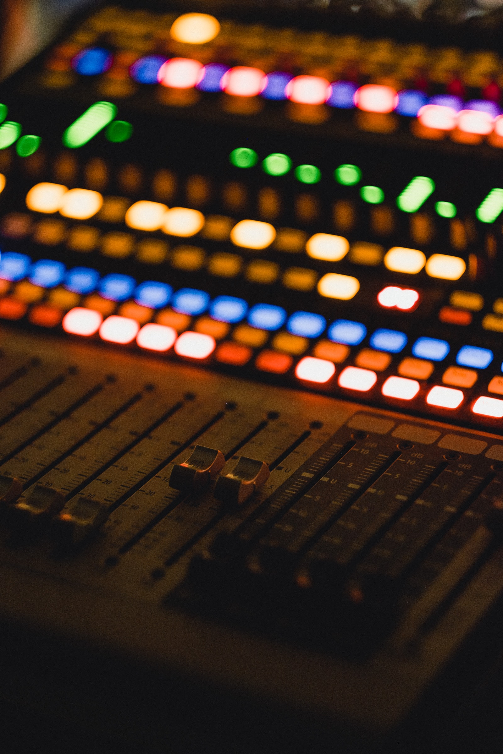 A close-up of a music mixer with colorful flashing lights and dials