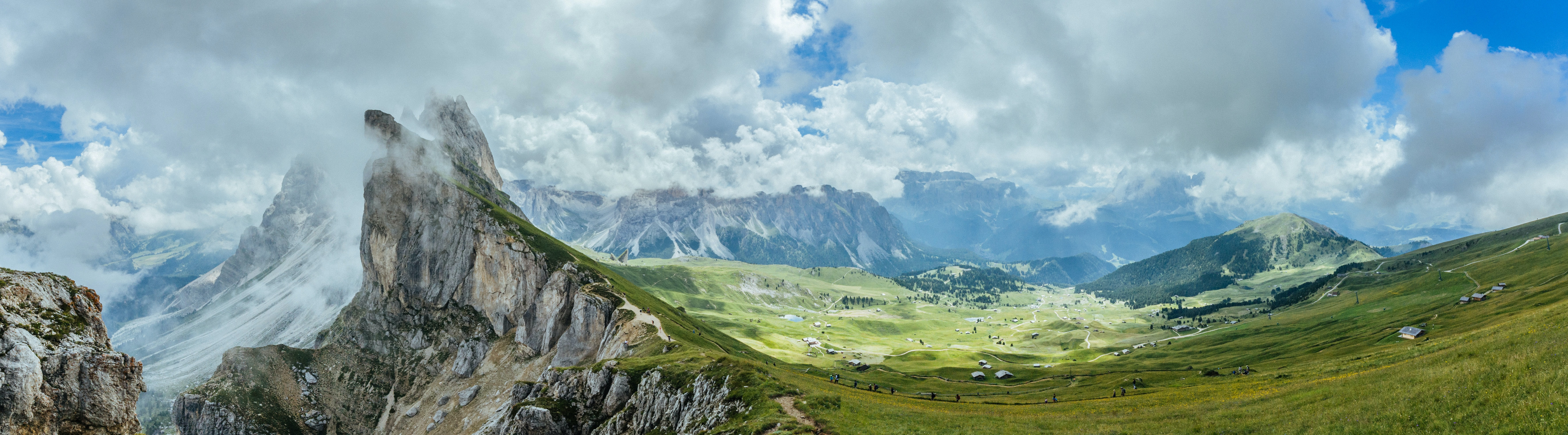 A beautiful mountainous landscape with white fluffy clouds over green fields and tall peaks in Seceda