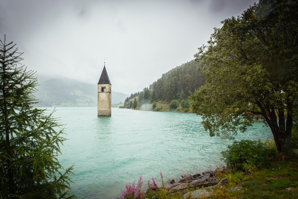 concrete tower surrounded by water near land with trees