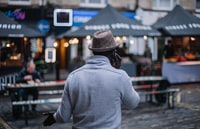 shallow focus photography of man walking in front of establishments