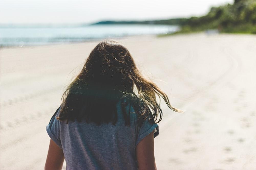 woman walking in seashore during daytime