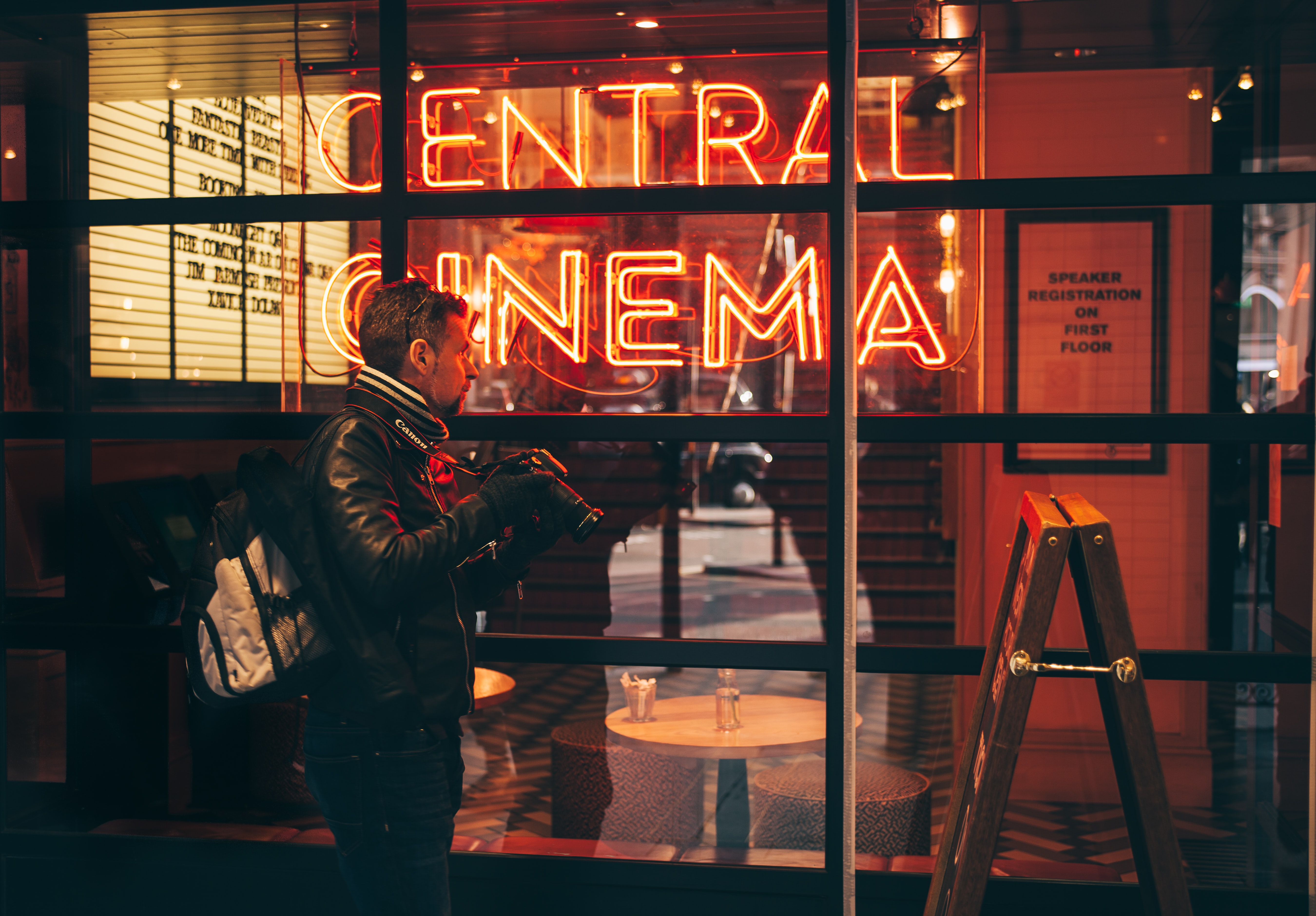 """Man in jacket with camera stands in front of neon """"Central Cinema"""" sign in Piccadilly"""