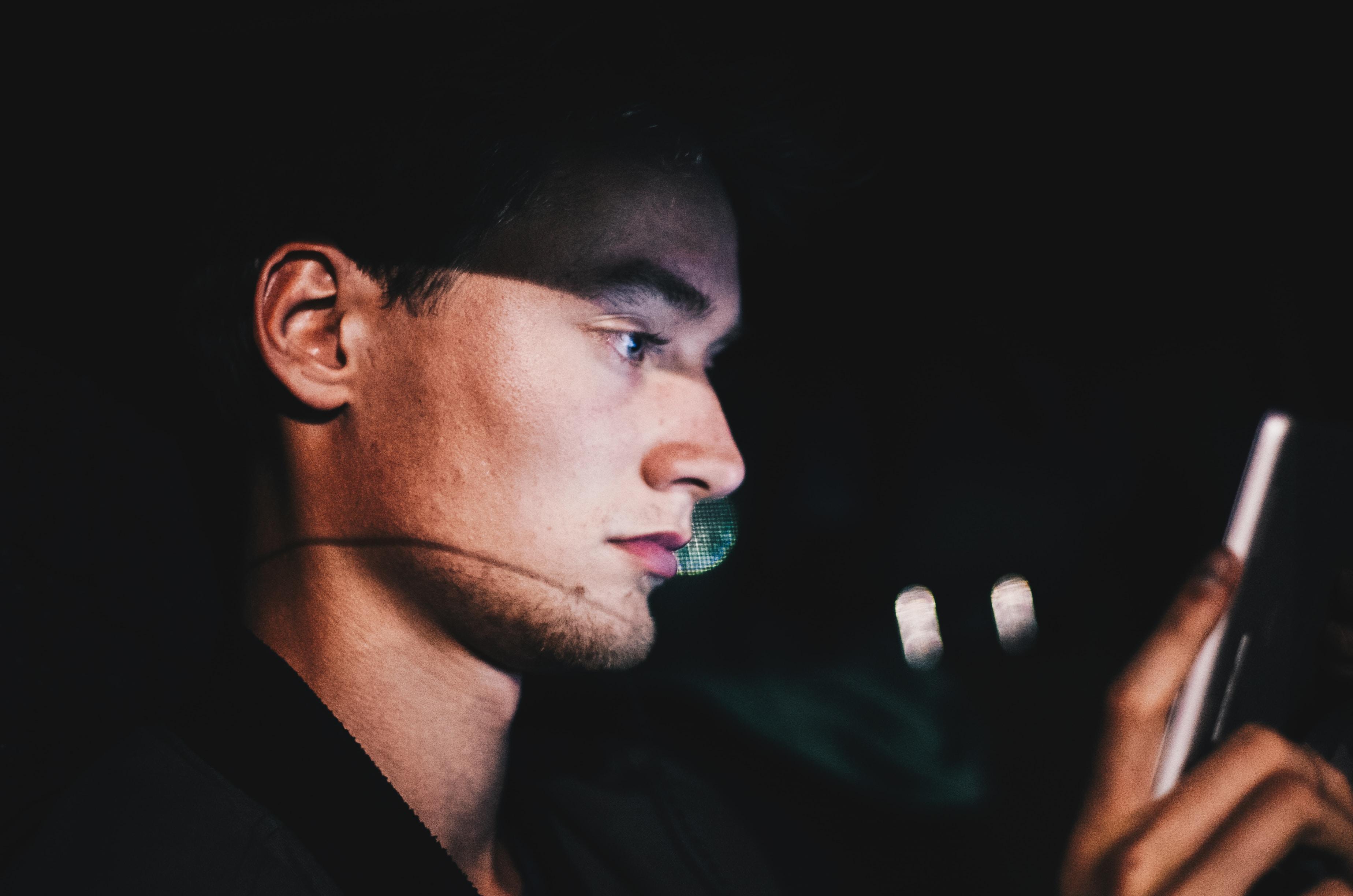 man using phone during nighttime