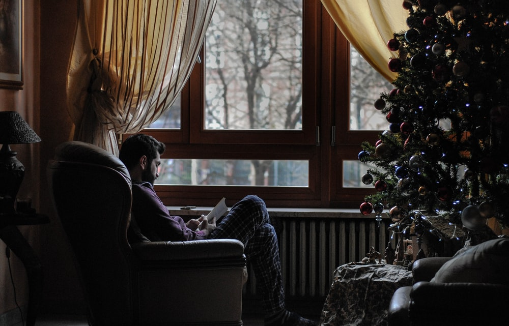 Man reading a book, sitting by the window during Christmas at Metropolitan City of Turin
