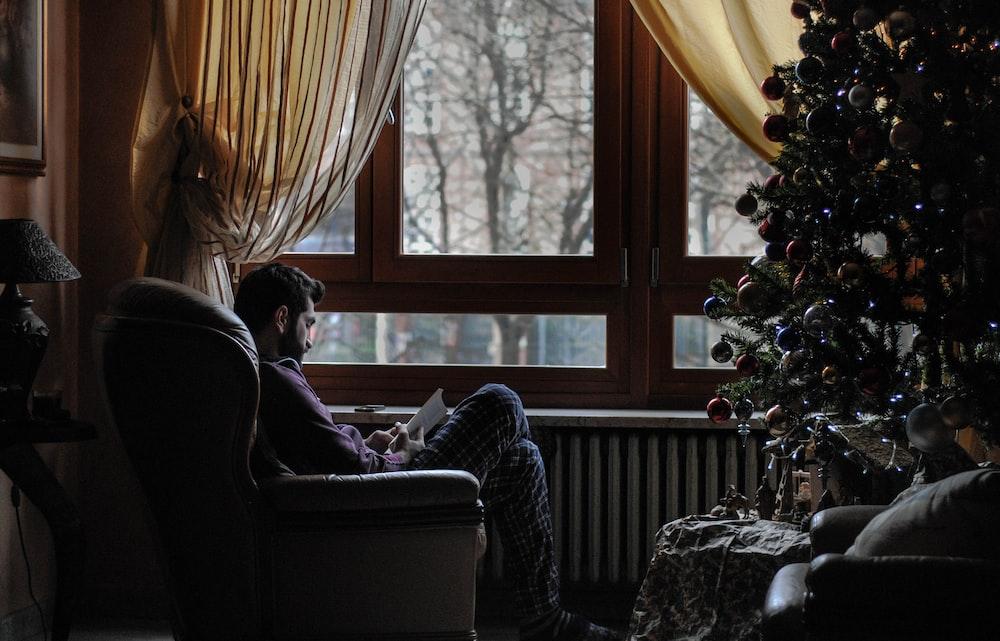 man sitting on sofa chair near Christmas tree
