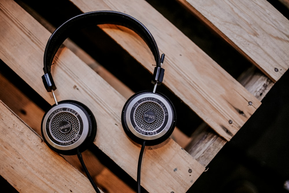 gray and black corded headphones on top of brown wooden surface