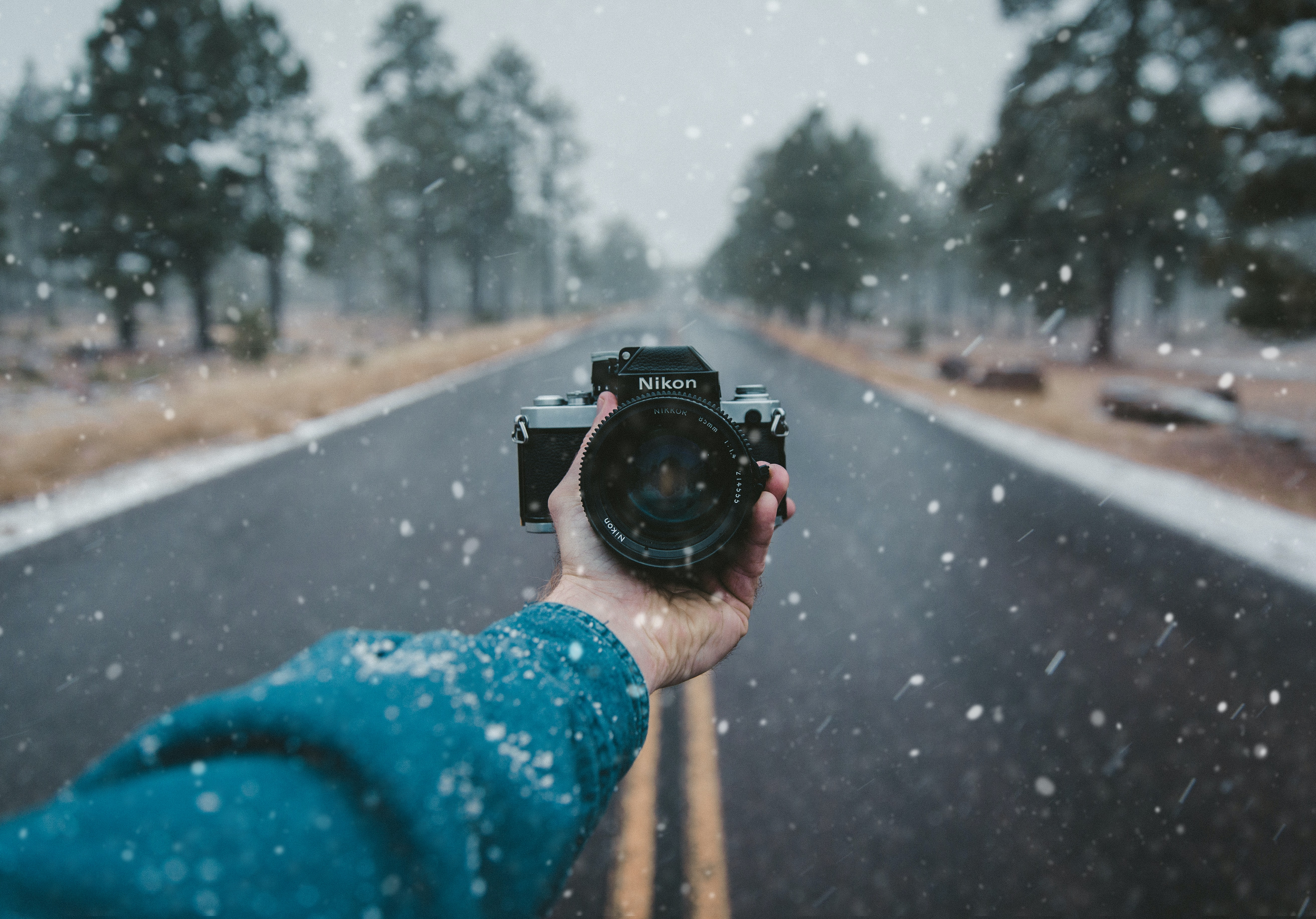 A Nikon camera is held facing the photographer standing on an empty road in the snow.