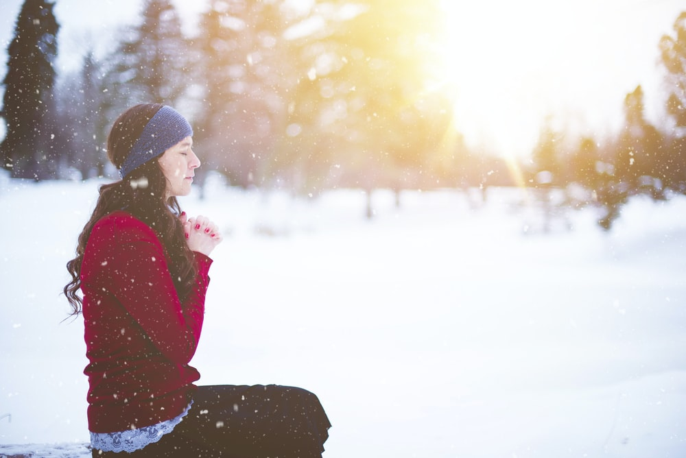 A woman wearing a blue headband and red sweatshirt, holding her hands together in prayer while sitting outside on a snowy day