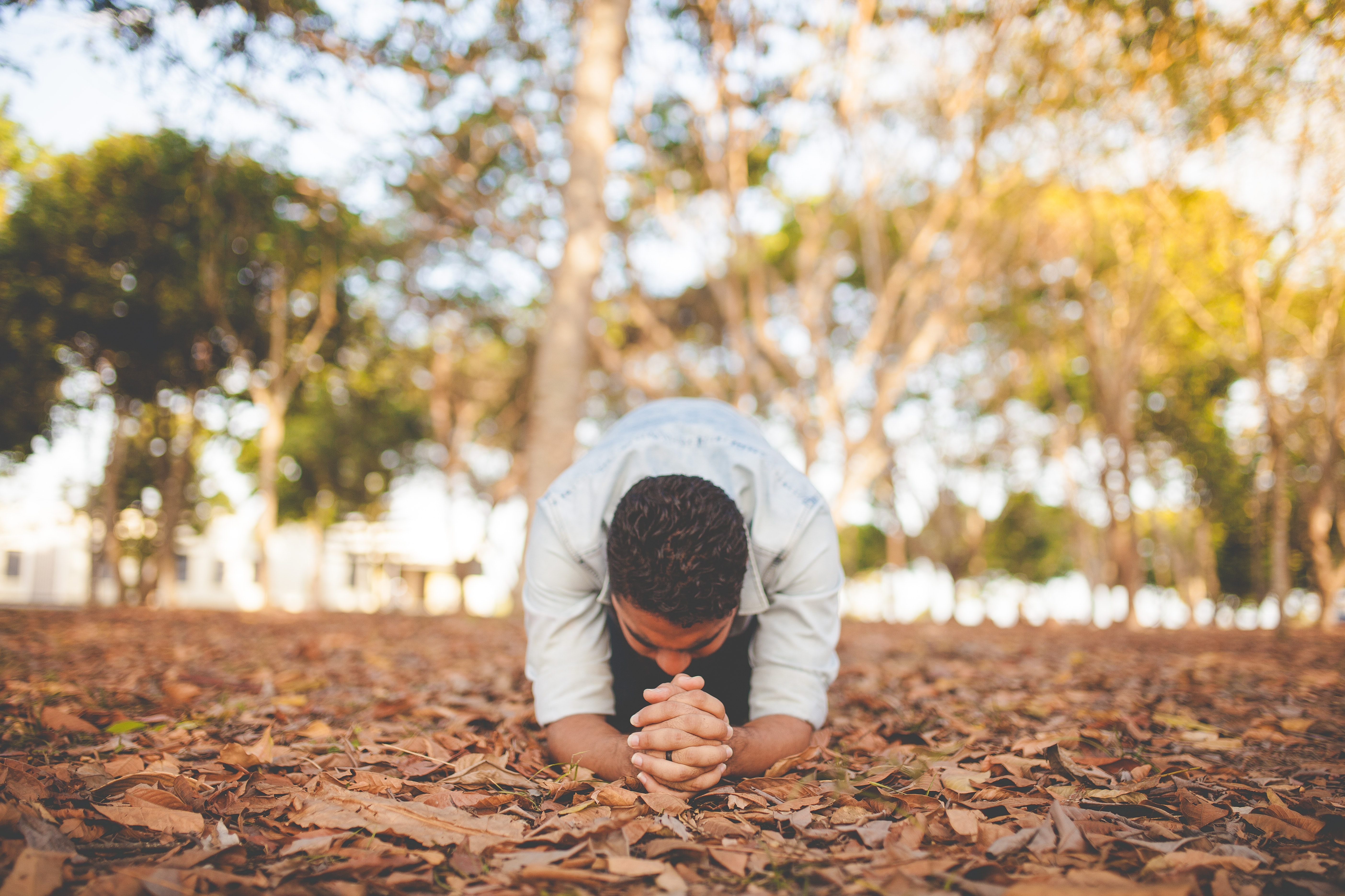 Man kneeling in leaves the ground with hands folded in prayer