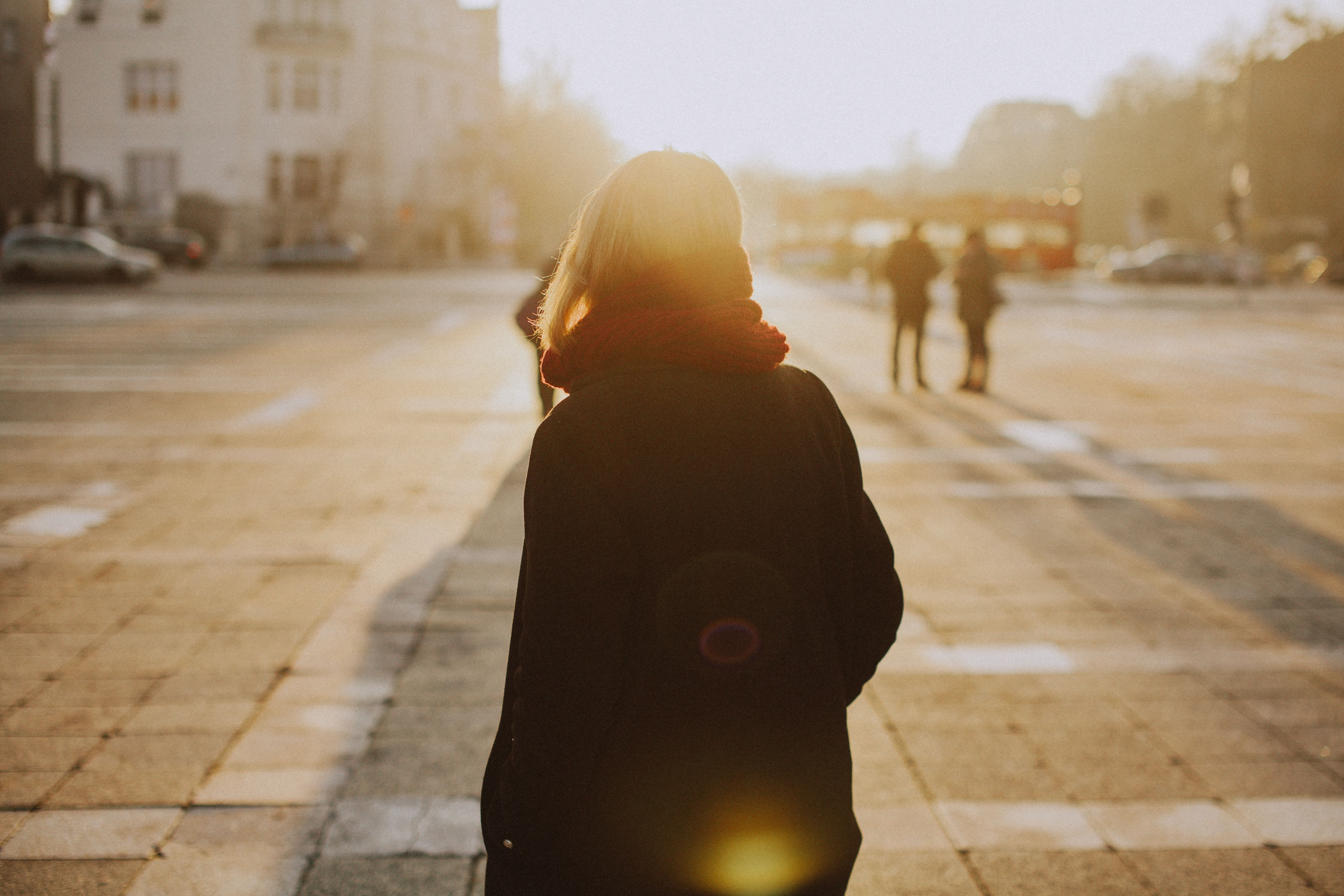 A woman in a scarf in a Budapest city square faces away toward the sunset