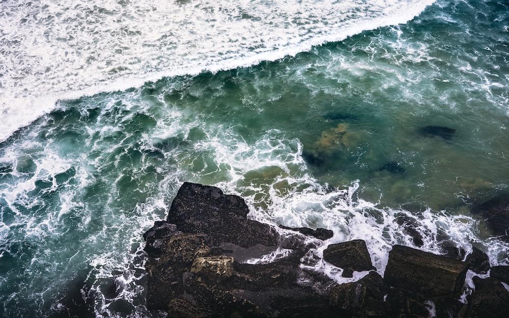 bird's-eye photography of rocks beside body of water