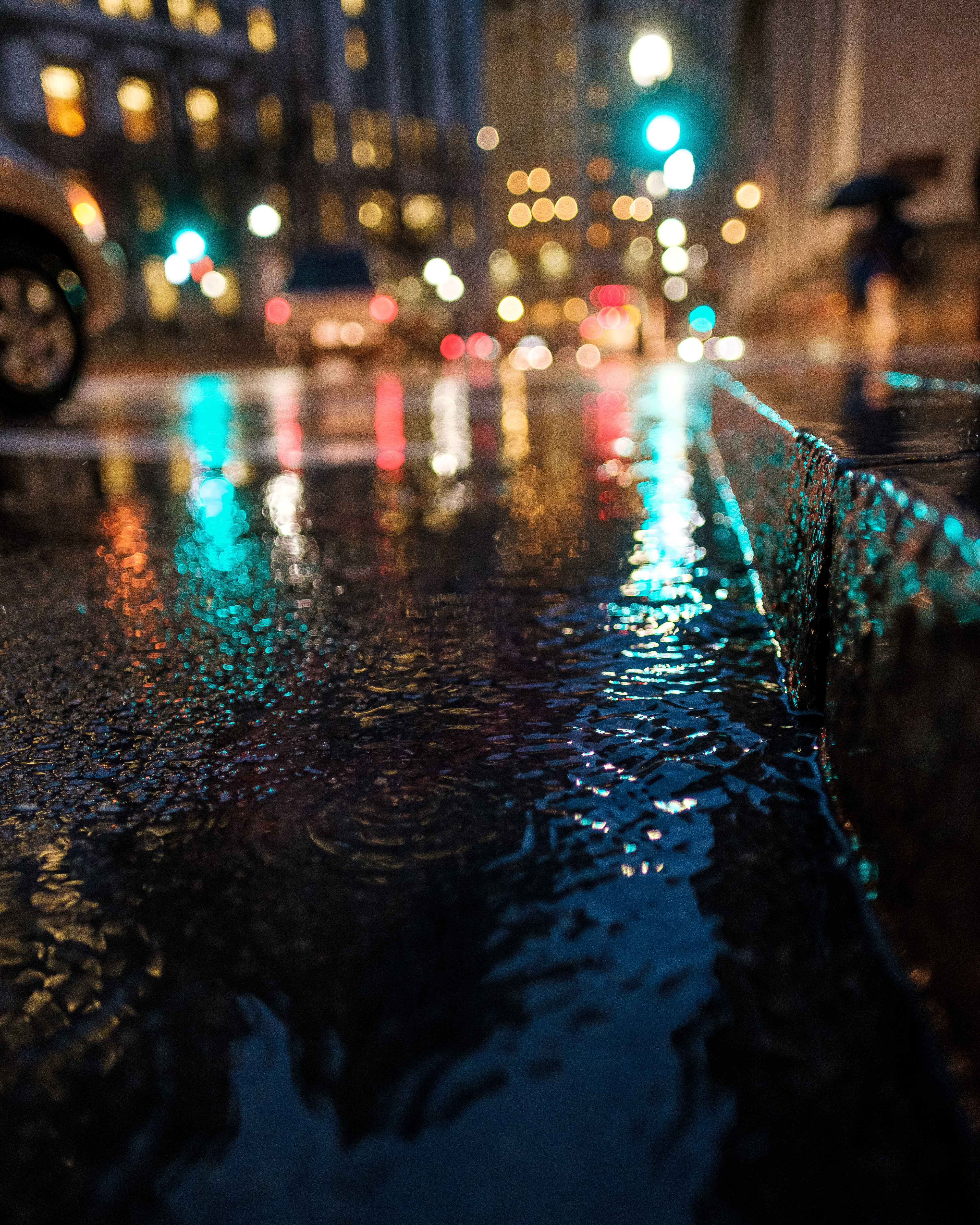 A night-time image capturing the rain on the ground on a downtown street.