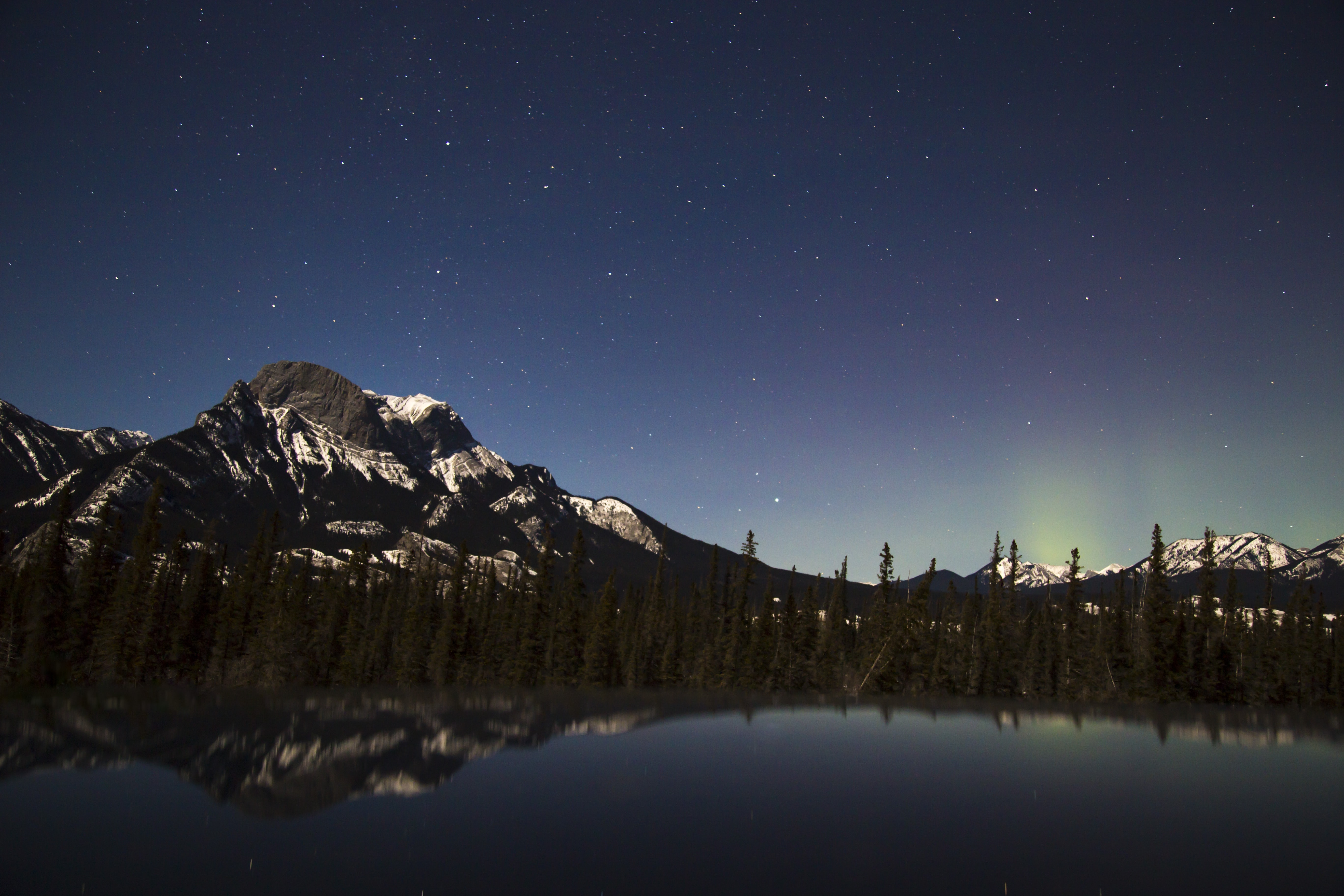 A scenic landscape with a lake and a mountain under a starry sky in Jasper