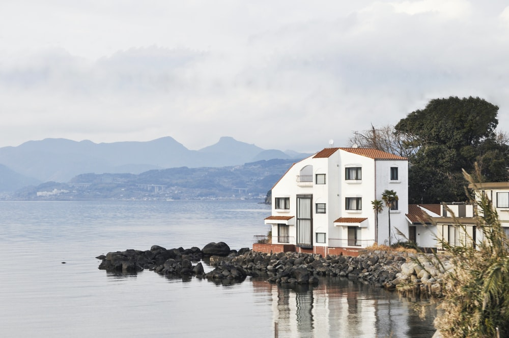 white and brown house at lakeside under grey cloudy sky