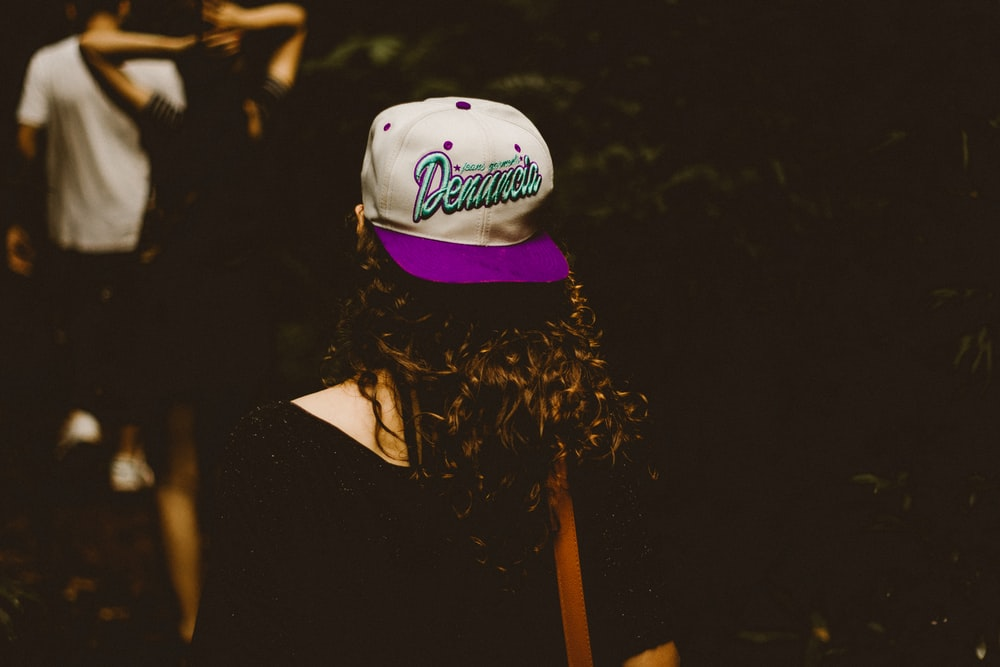 woman wearing white and purple fitted cap