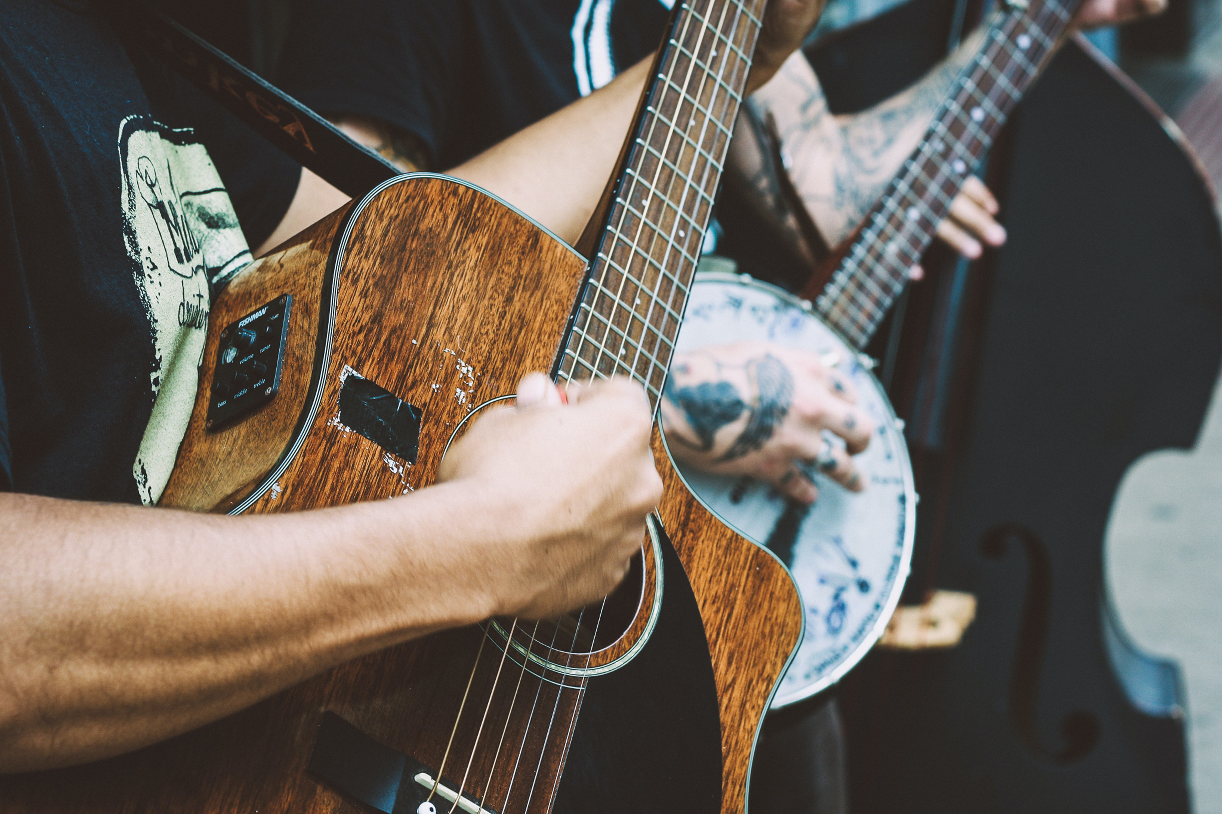 A close-up of a man's hand clutching a pick and playing a worn-out acoustic guitar
