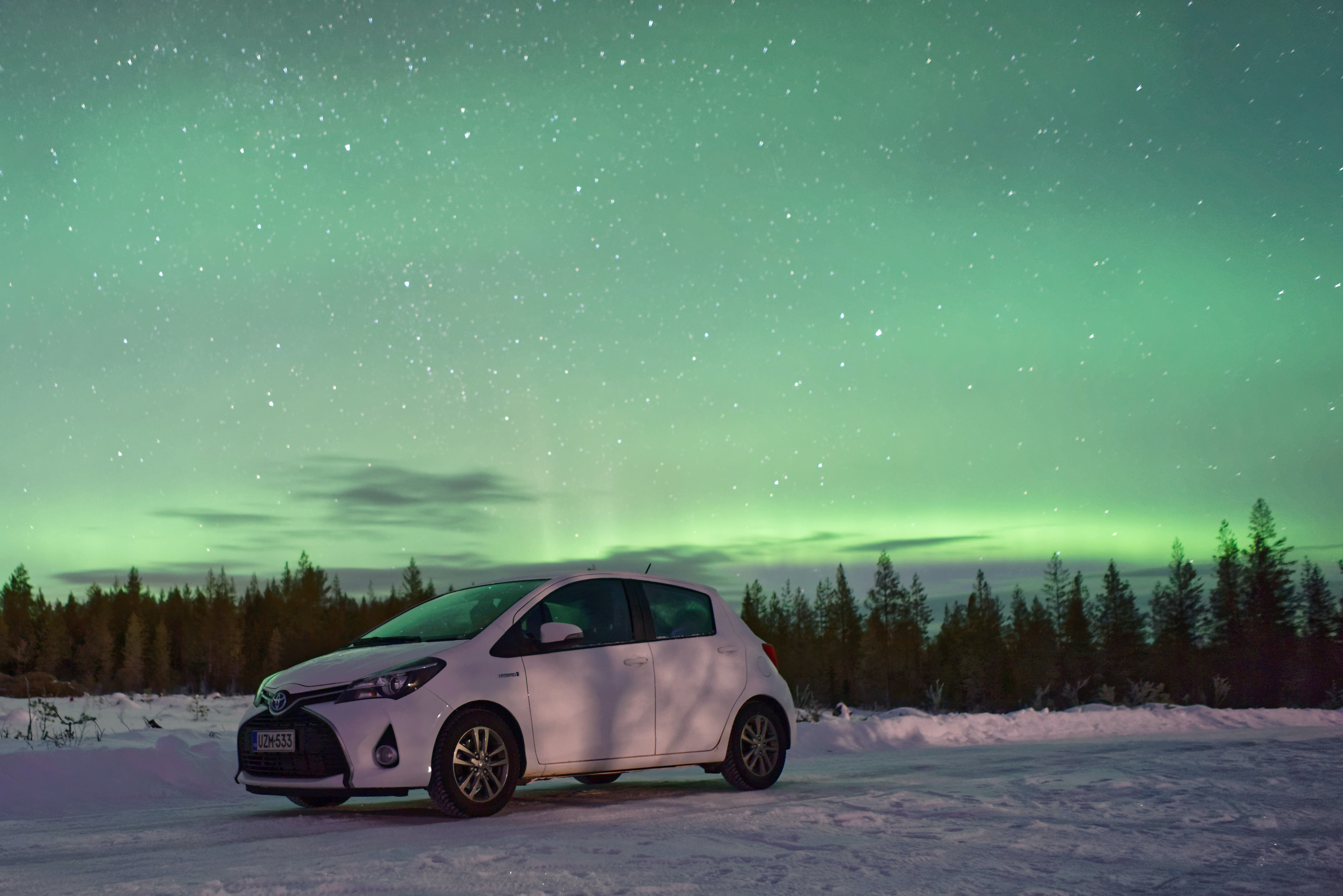 A newer white hatchback parked in the snow with a bright Aurora Boreali in the sky above