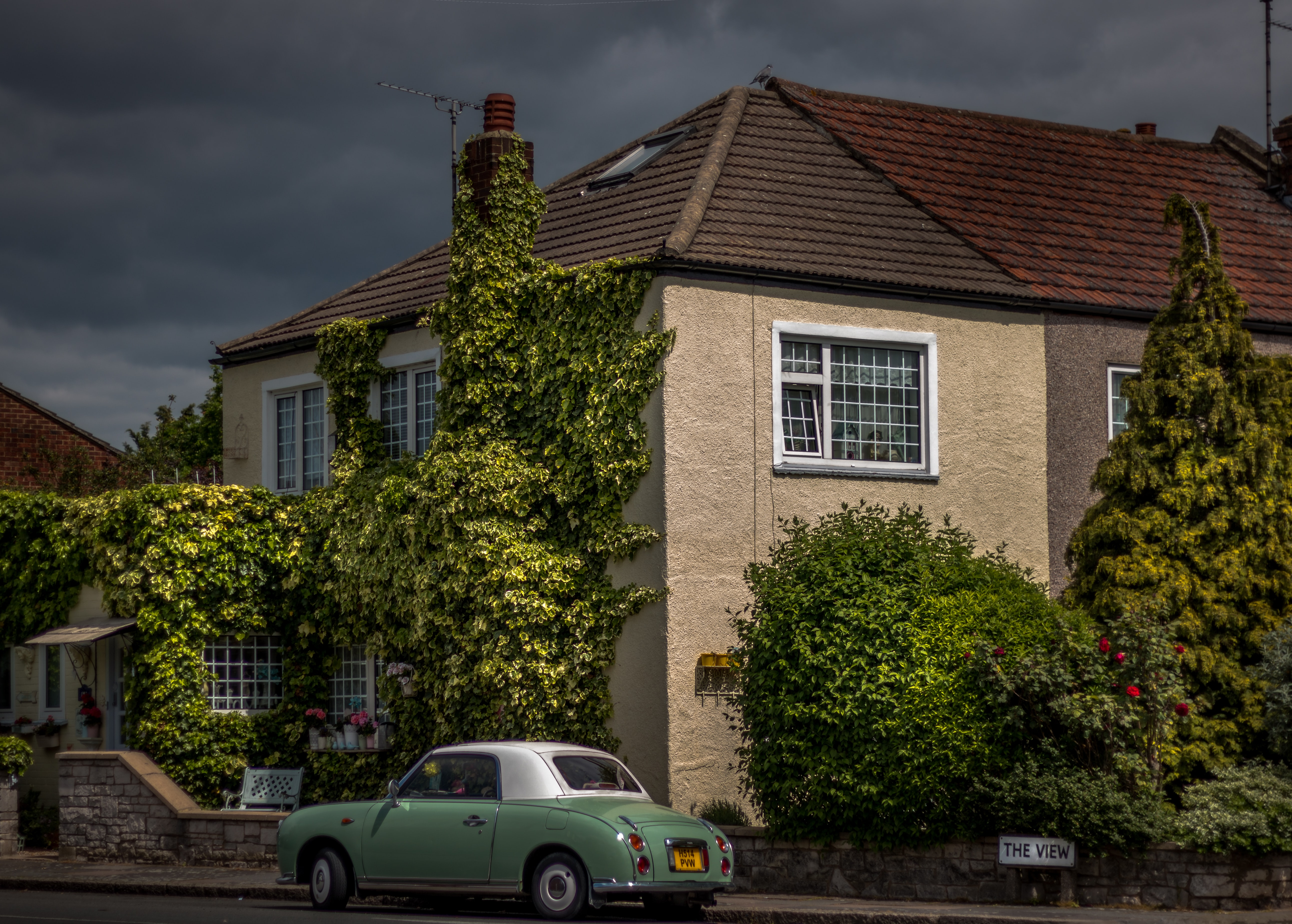 Old vintage car parked in front of the ivy-covered residential house in London