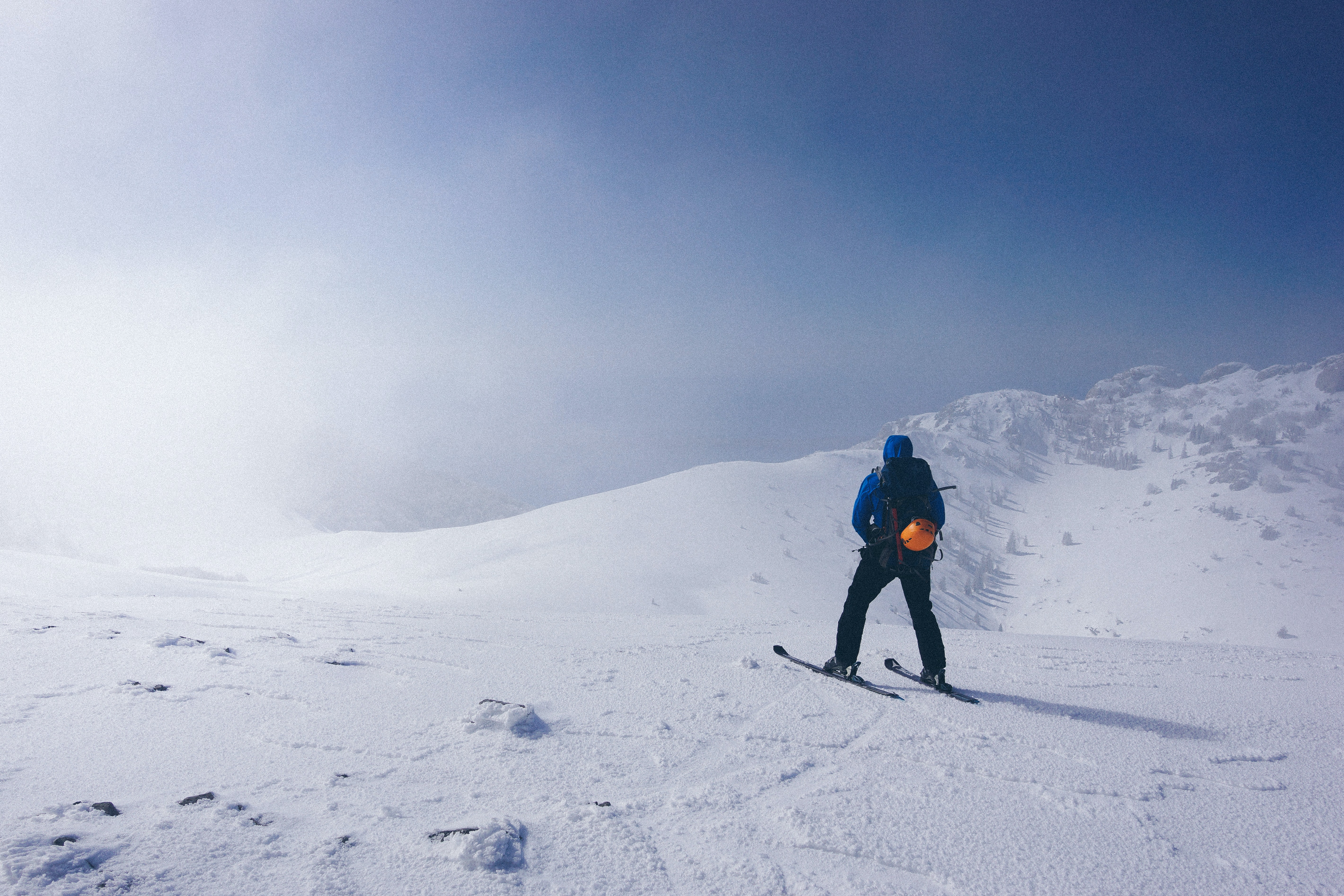 A man walking in skis on a slight slope near medium-sized mountains