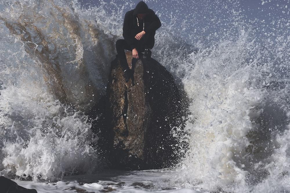 man seating on stone in between waving sea