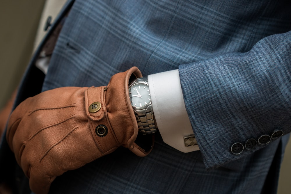 person wearing blue leather gloves with watch