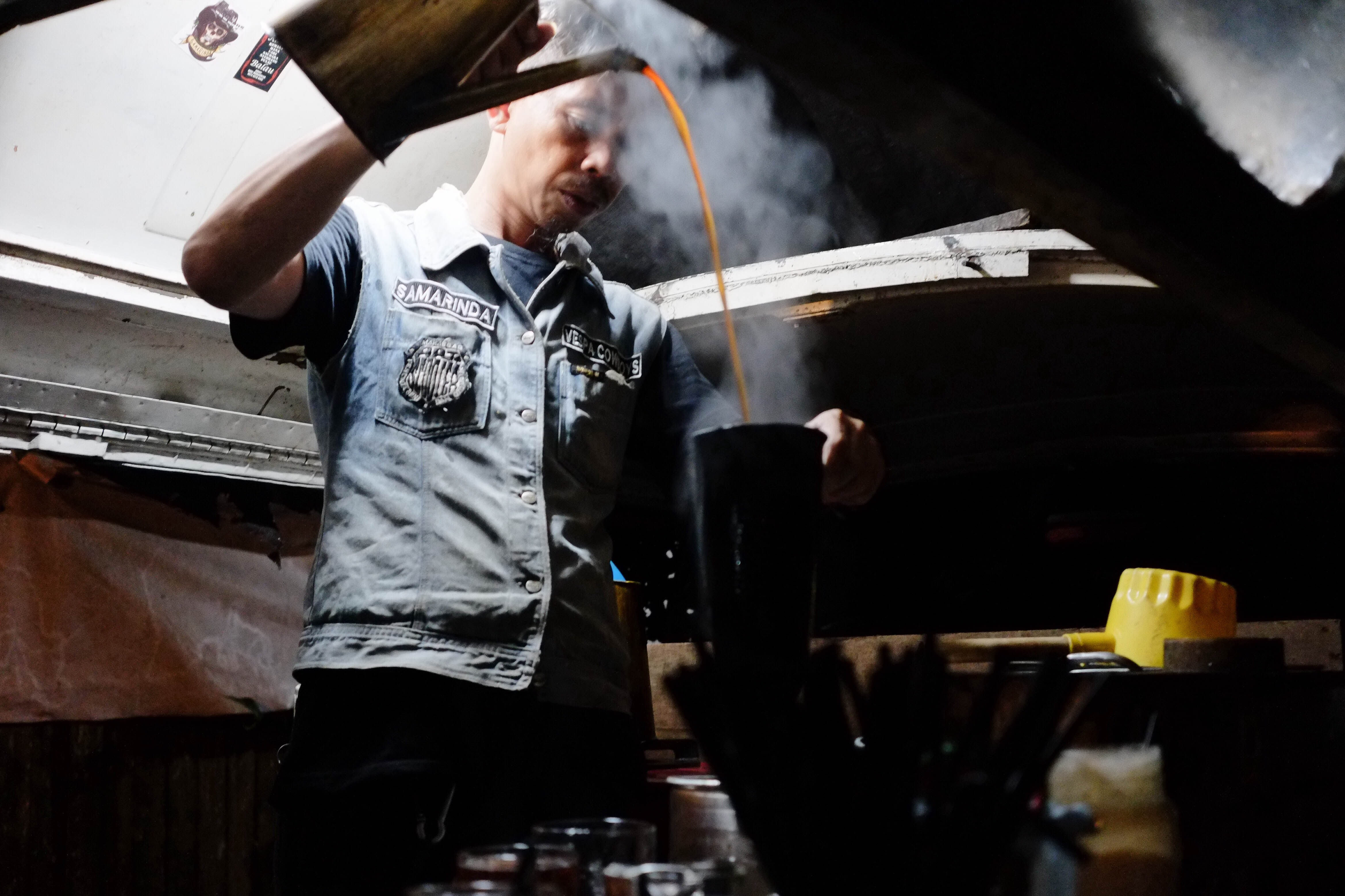 A man in a jean vest pours steaming coffee from a kettle in Samarinda