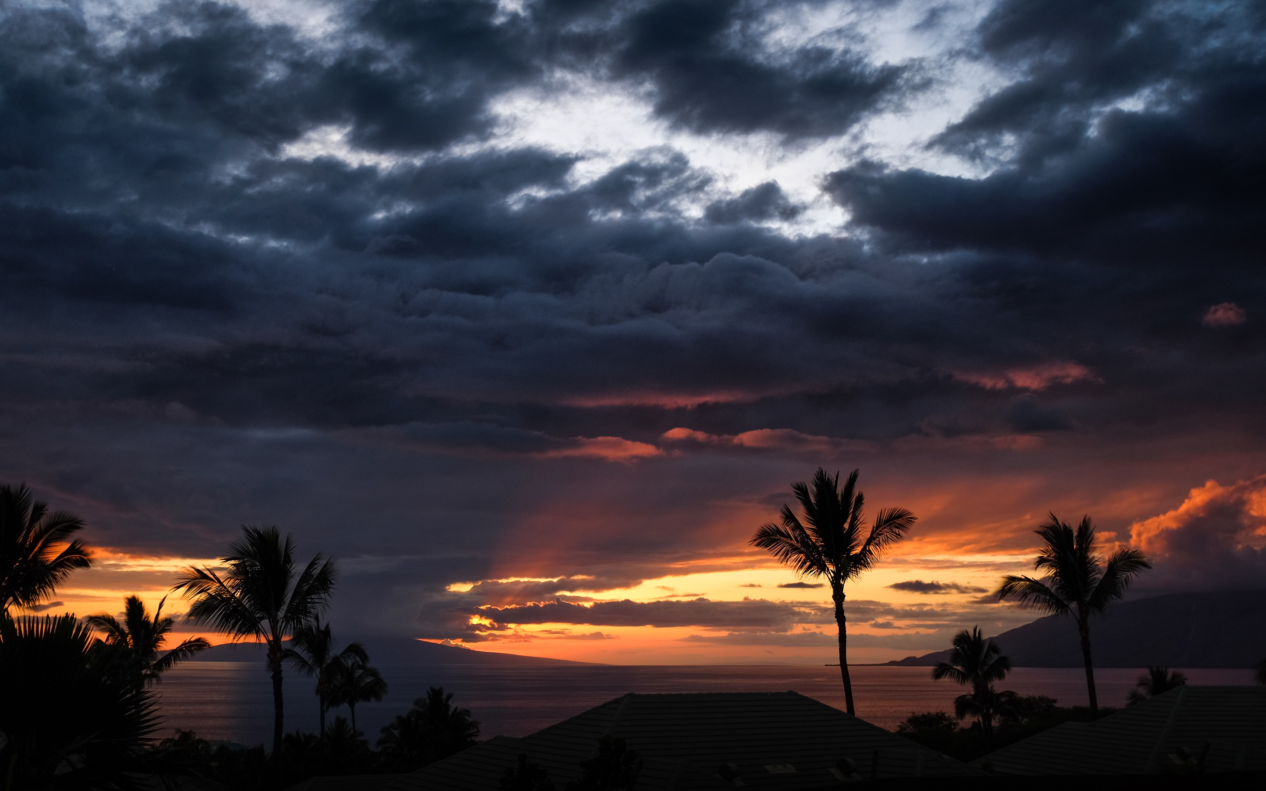 A cloudy sunset over silhouetted palm trees and hills at Wailea-Makena