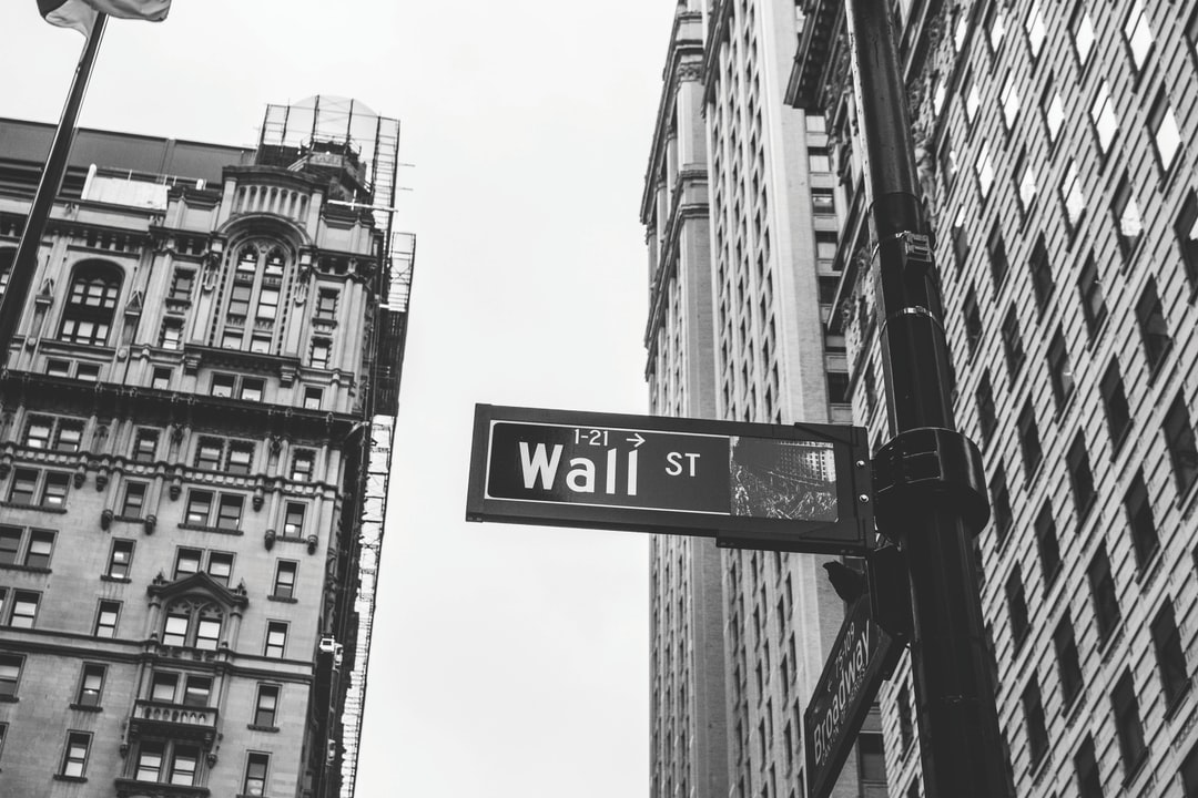 A street sign pointing to Wall Street in black and white