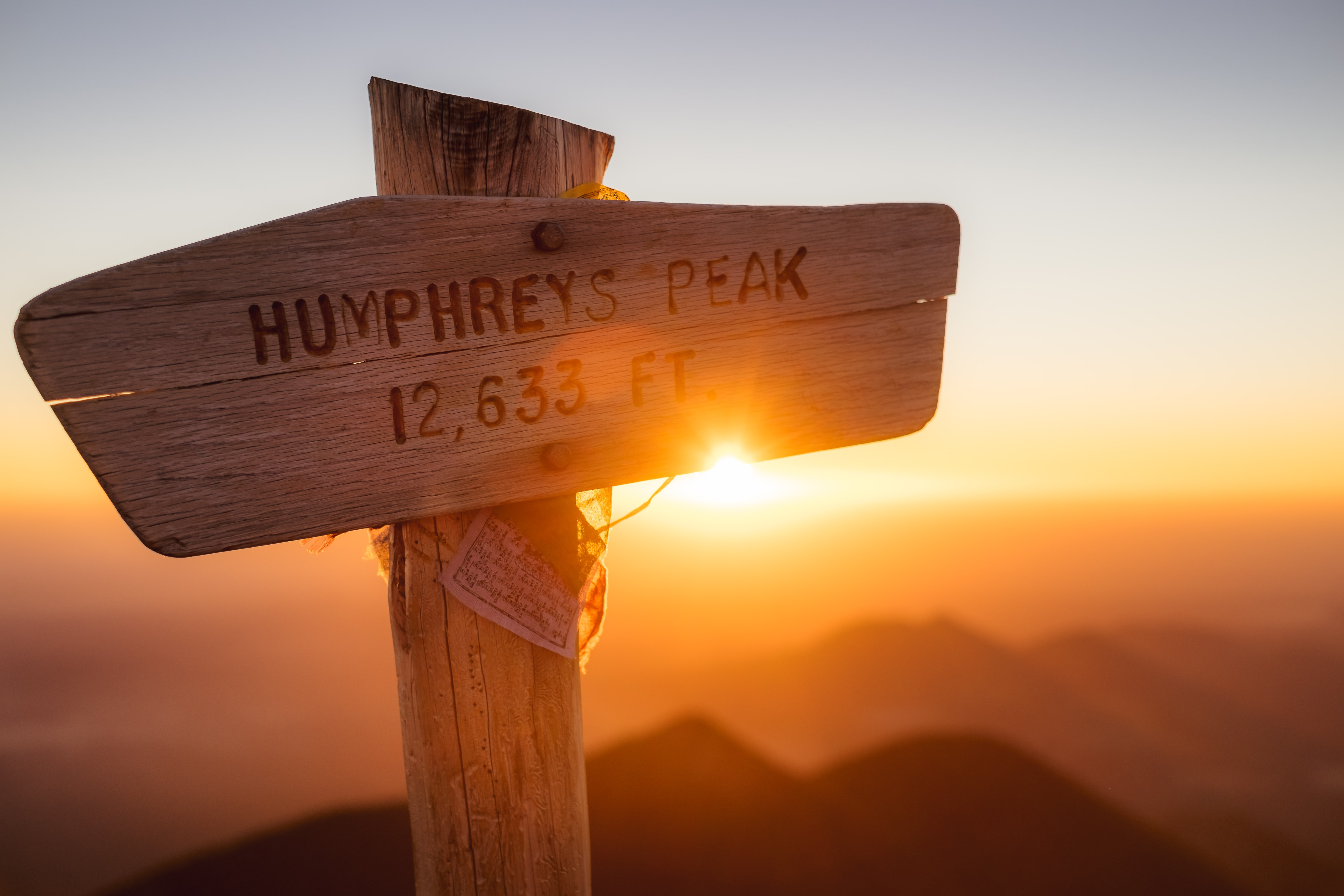 "A wooden signpost reading ""Humphreys Peak 12,633 ft"" during sunrise"