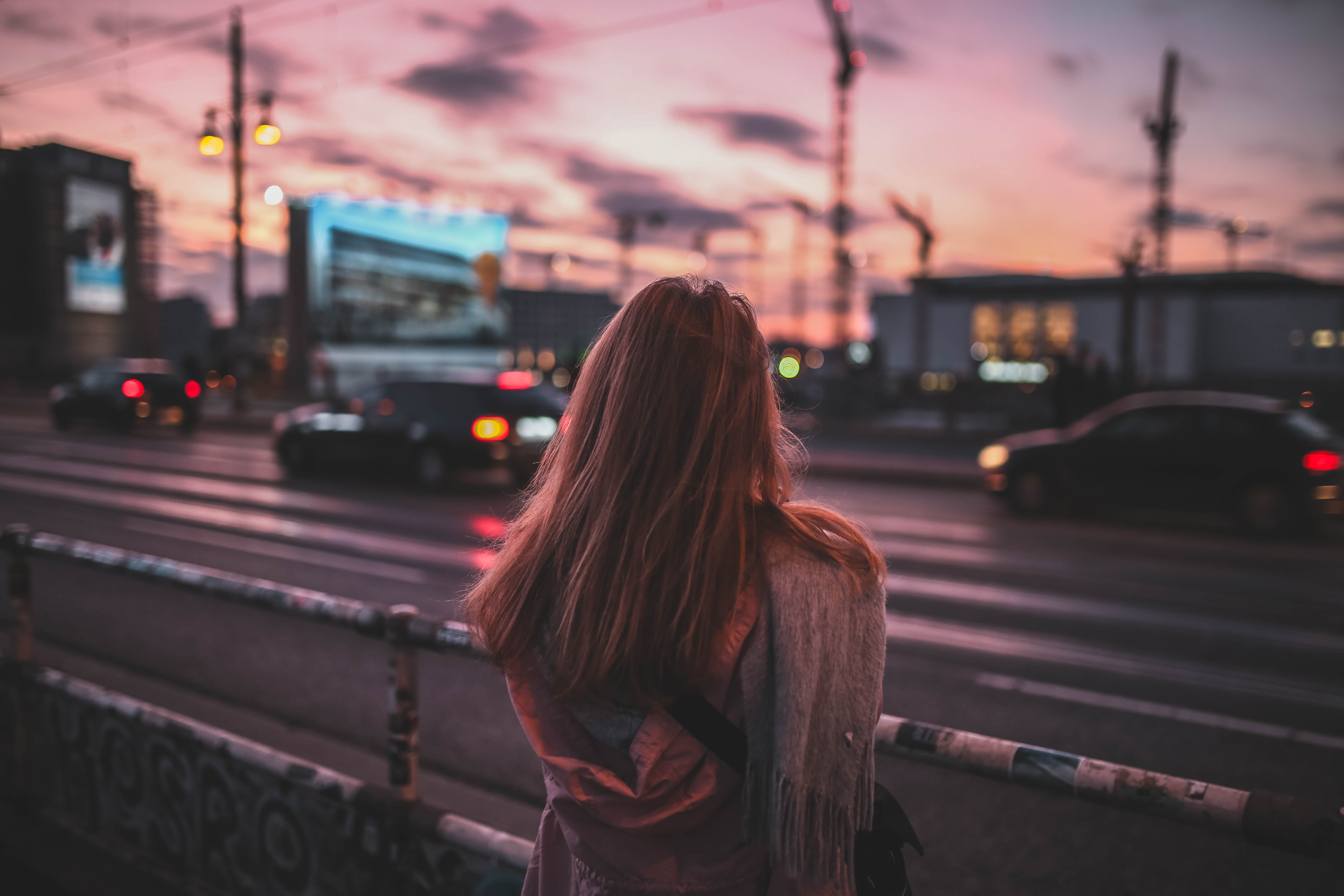 woman standing on rail facing road at dusk