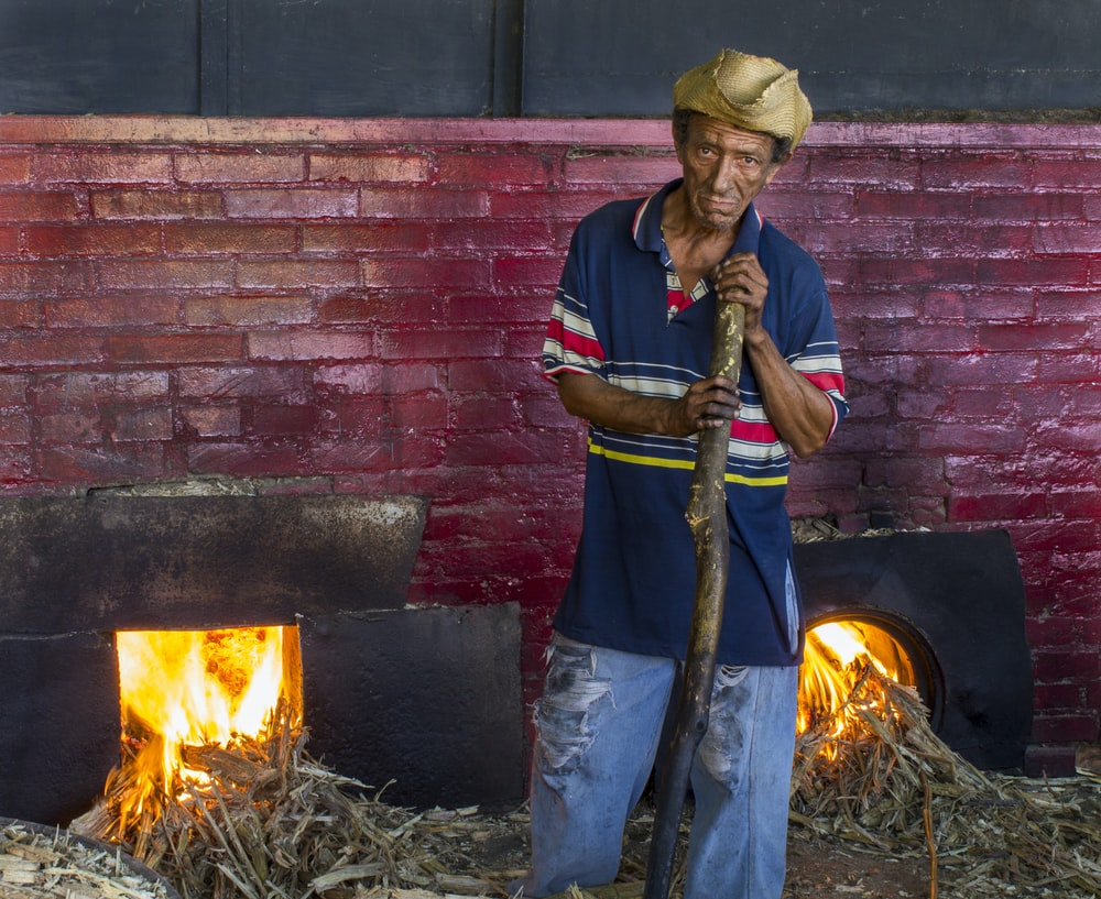 man wearing blue polo shirt near firepit