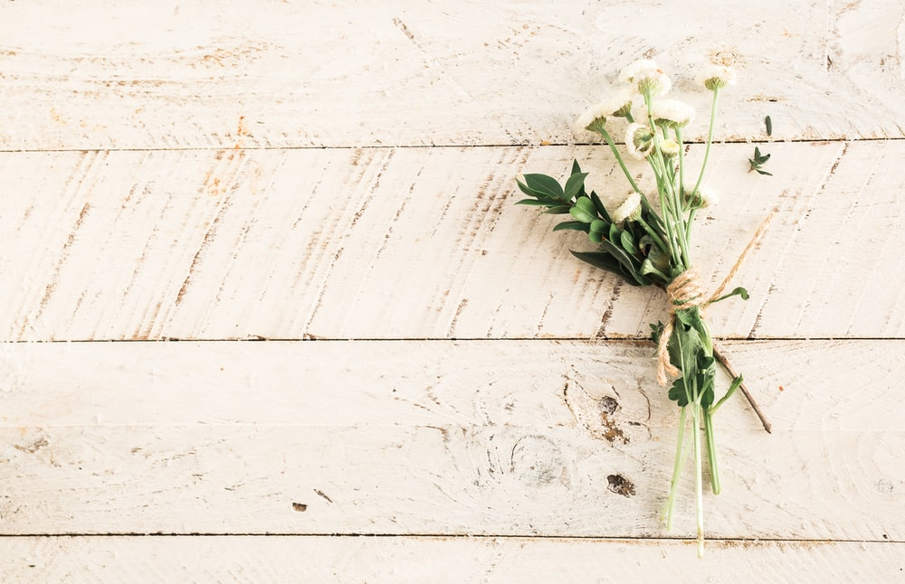 white flower bouquet on wooden surface