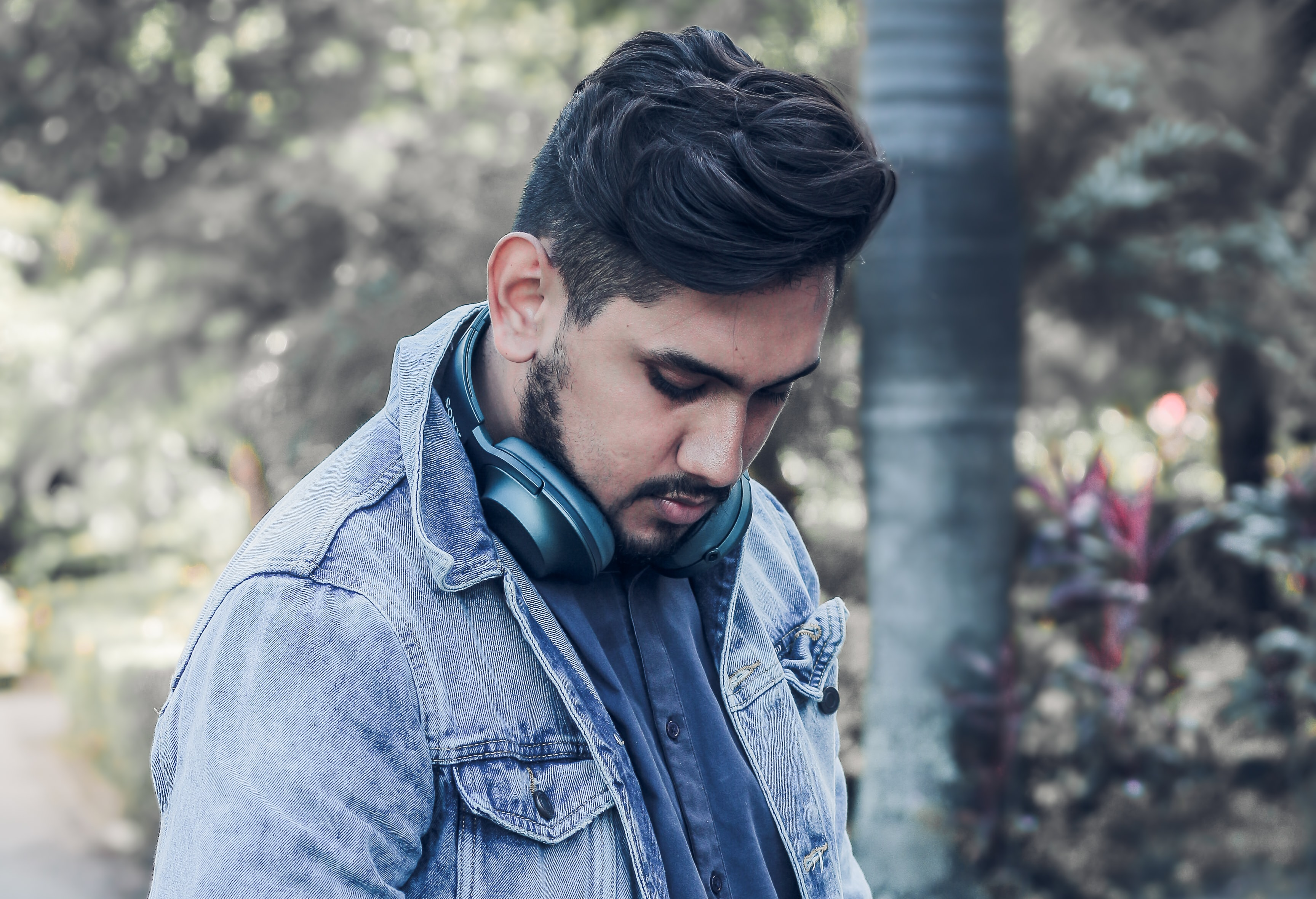 Man with tousled hairstyle wearing headphones around his neck